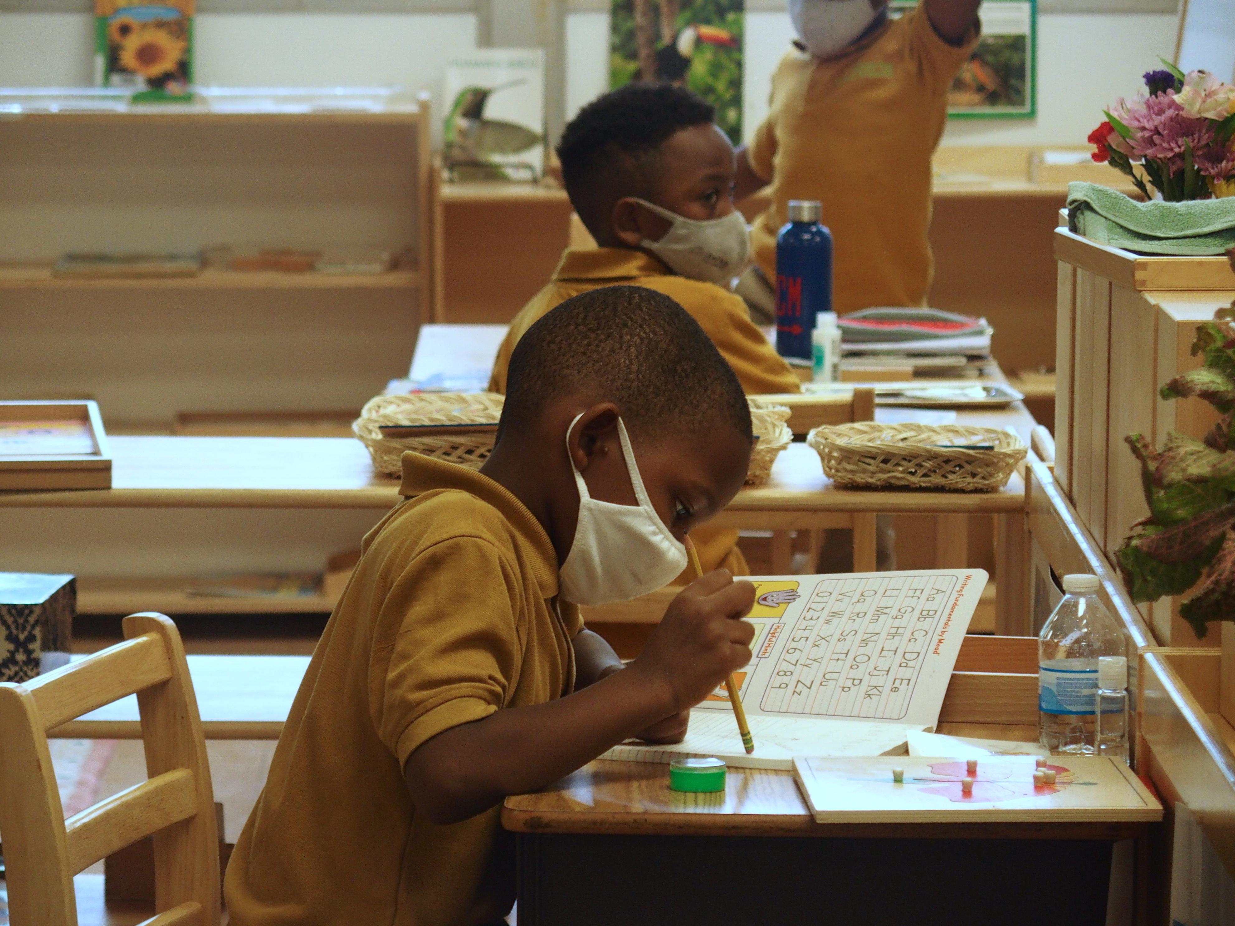Elementary school students in masks work at their desks