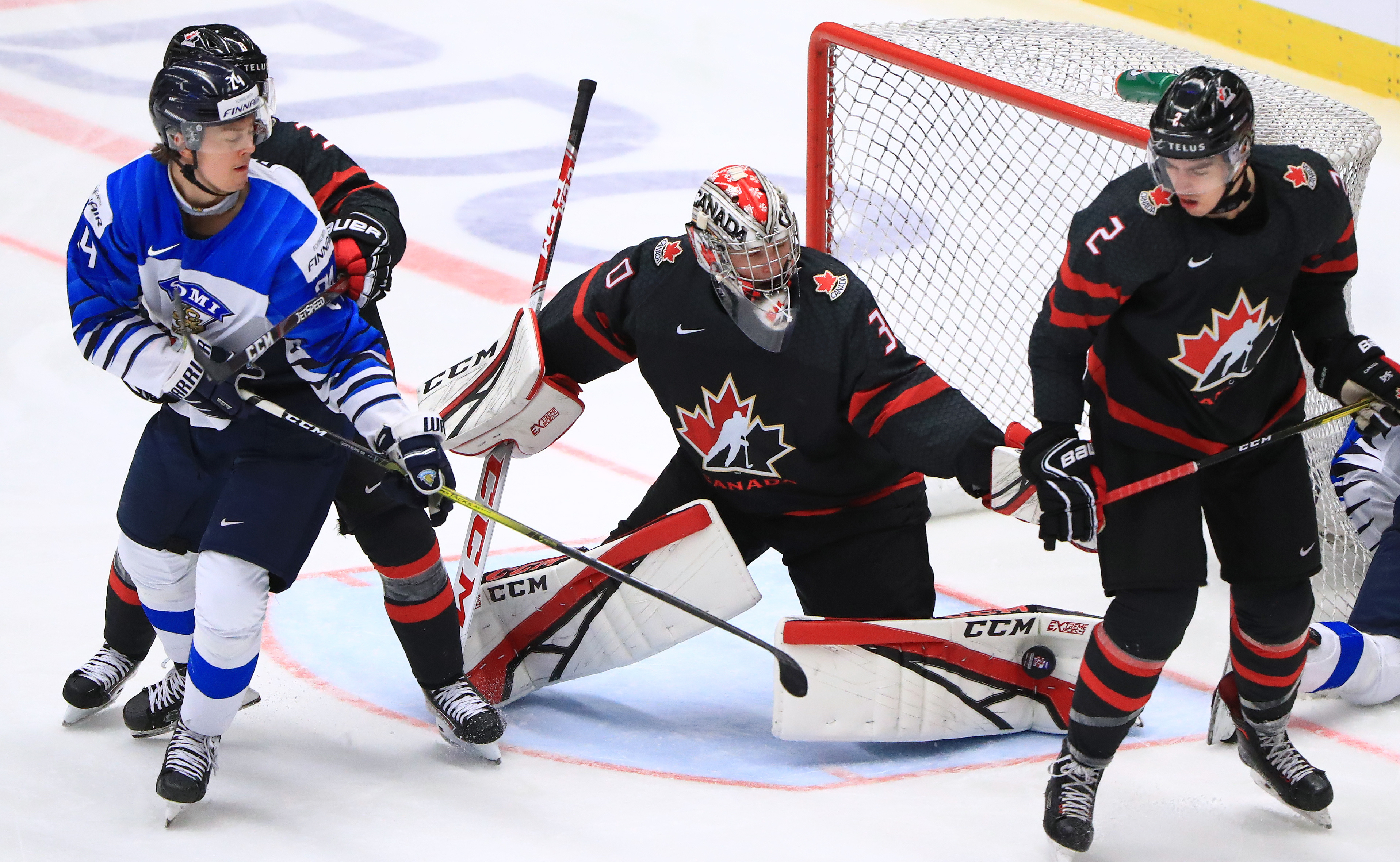 OSTRAVA, CZECH REPUBLIC - JANUARY 4, 2020: Finland's Sampo Ranta (L) and Canada's Kevin Bahl, goalie Joel Hofer (R-L) in their 2020 World Junior Ice Hockey Championship semifinal match at Ostravar Arena.