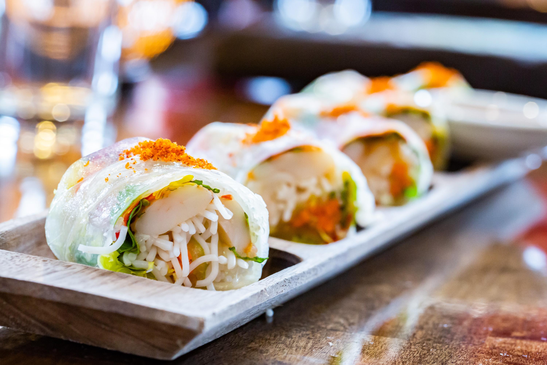 four tightly rolled Nasturtium Shrimp Spring Rolls on a rectangular wooden plate at Girl Diver in Atlanta