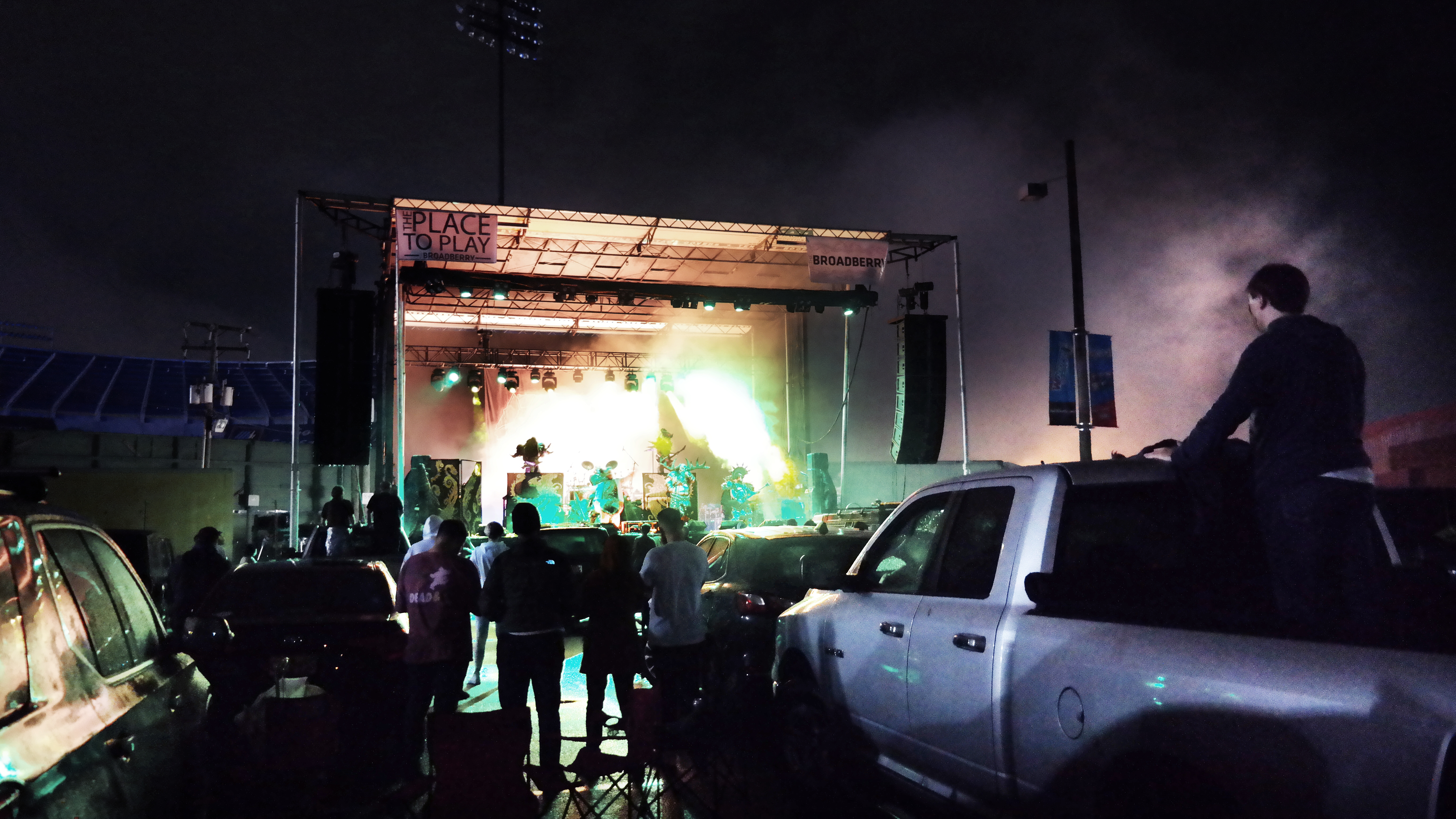 A brightly lit outdoor stage with cars and people in front of it during an evening concert.