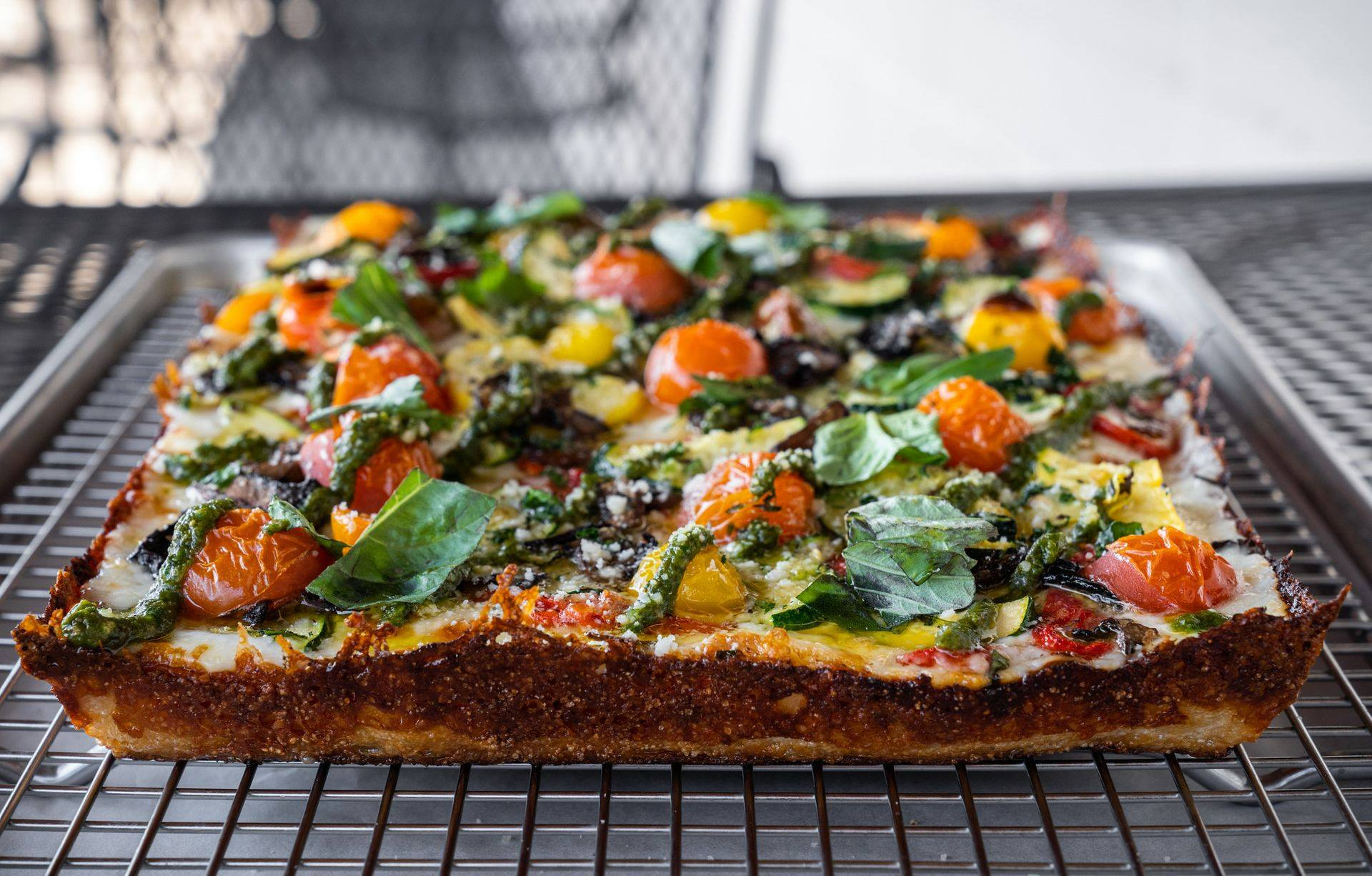 a Detroit-style pizza with crispy edges cooling on a wire rack. The pizza is topped with red and yellow cherry tomatoes and spinach