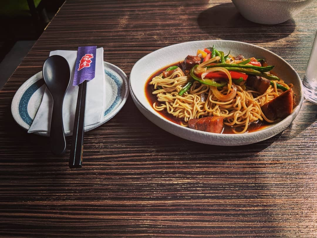 A table is set with a fork, spoon, and chopsticks on a saucer next to a large bowl of noodles topped with scallions, sliced bell peppers, in a dark broth
