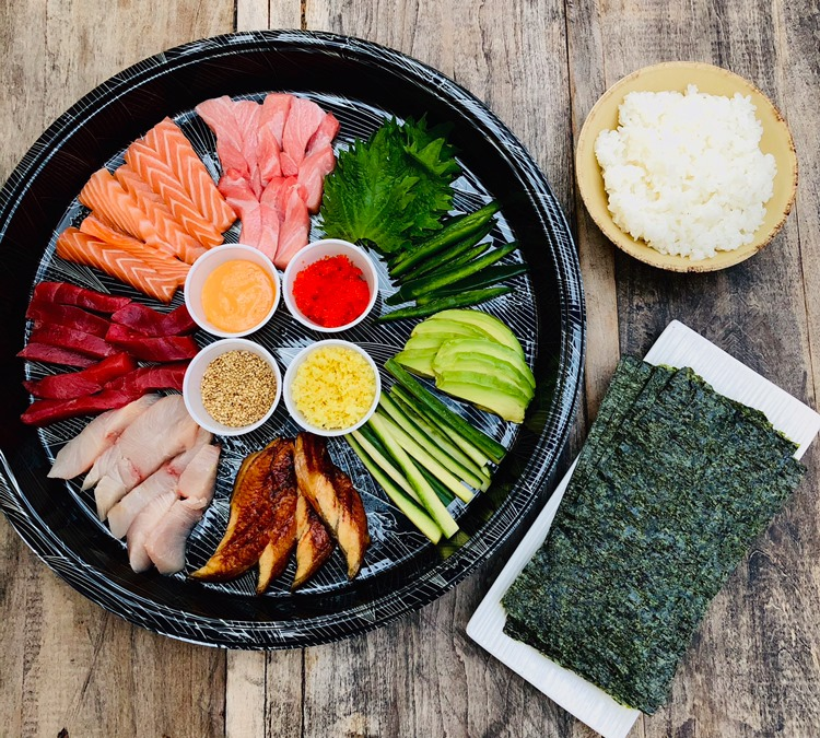 A colorful array of sliced raw fish, including salmon and tuna, along with julienned veggies on a black tray. A plate of crisped nori and bowl of rice sit to the side.