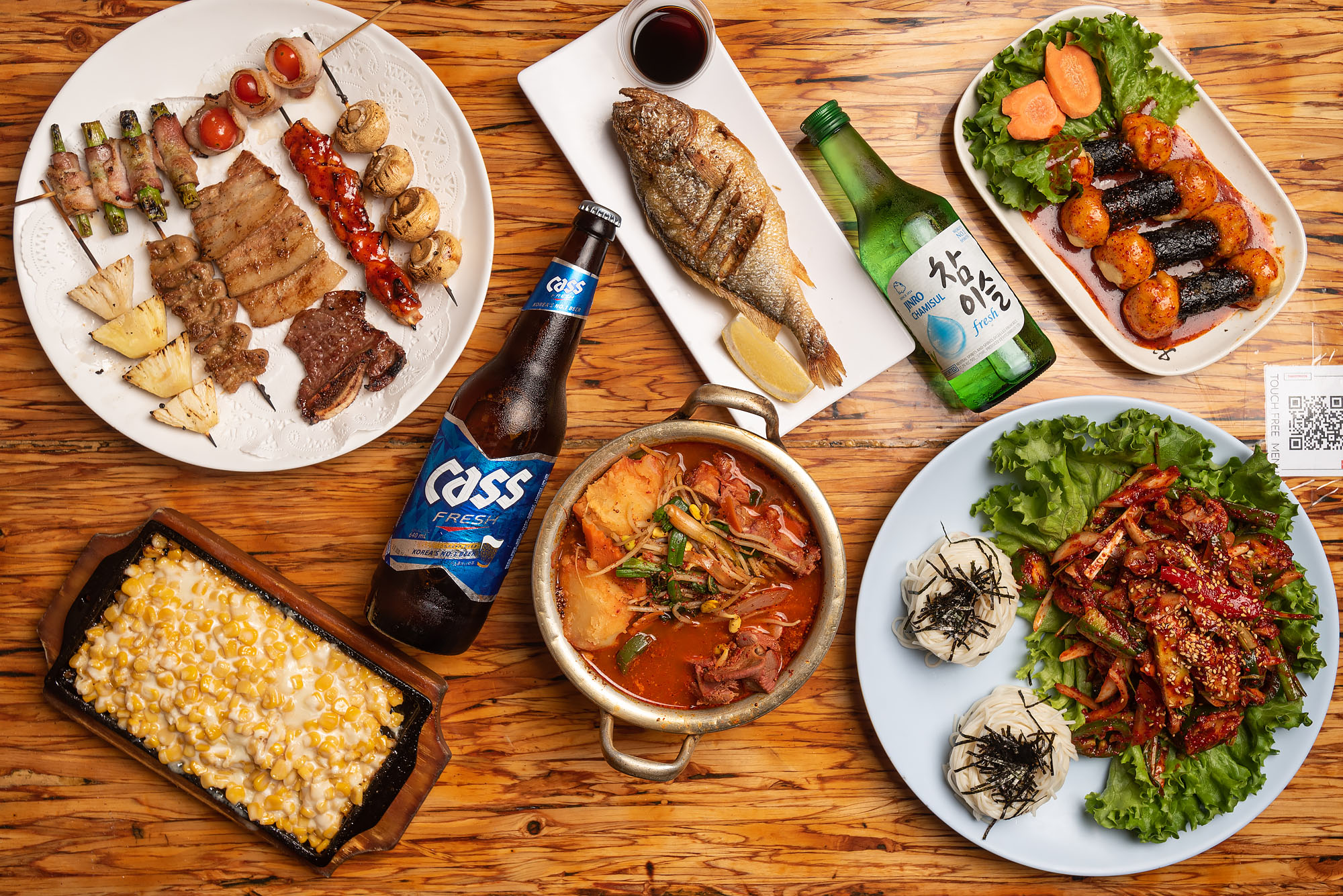 Dishes and Korean beer from Dan Sung Sa against a wooden table.