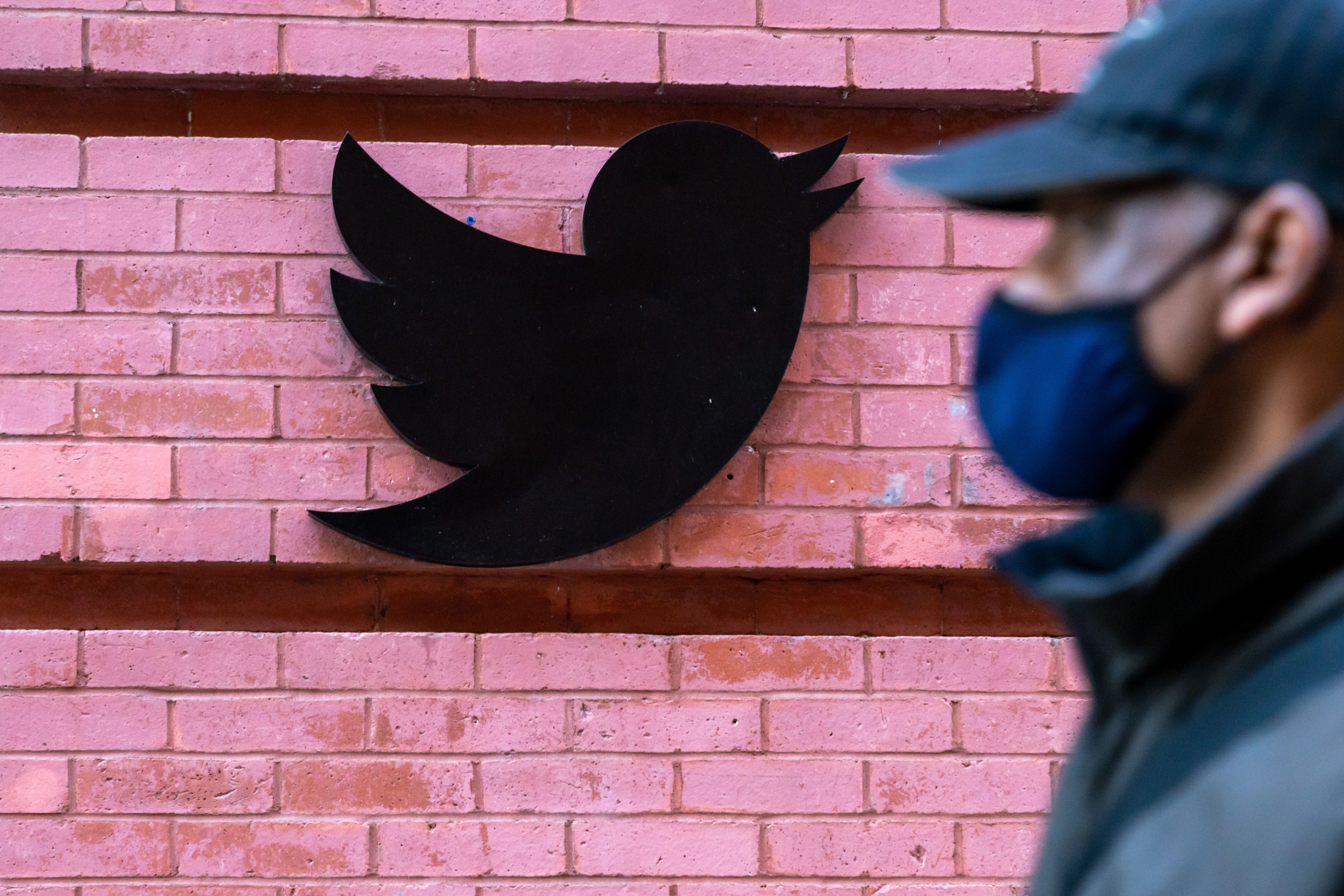 A man wearing a face mask walks past a Twitter logo on the side of a building.
