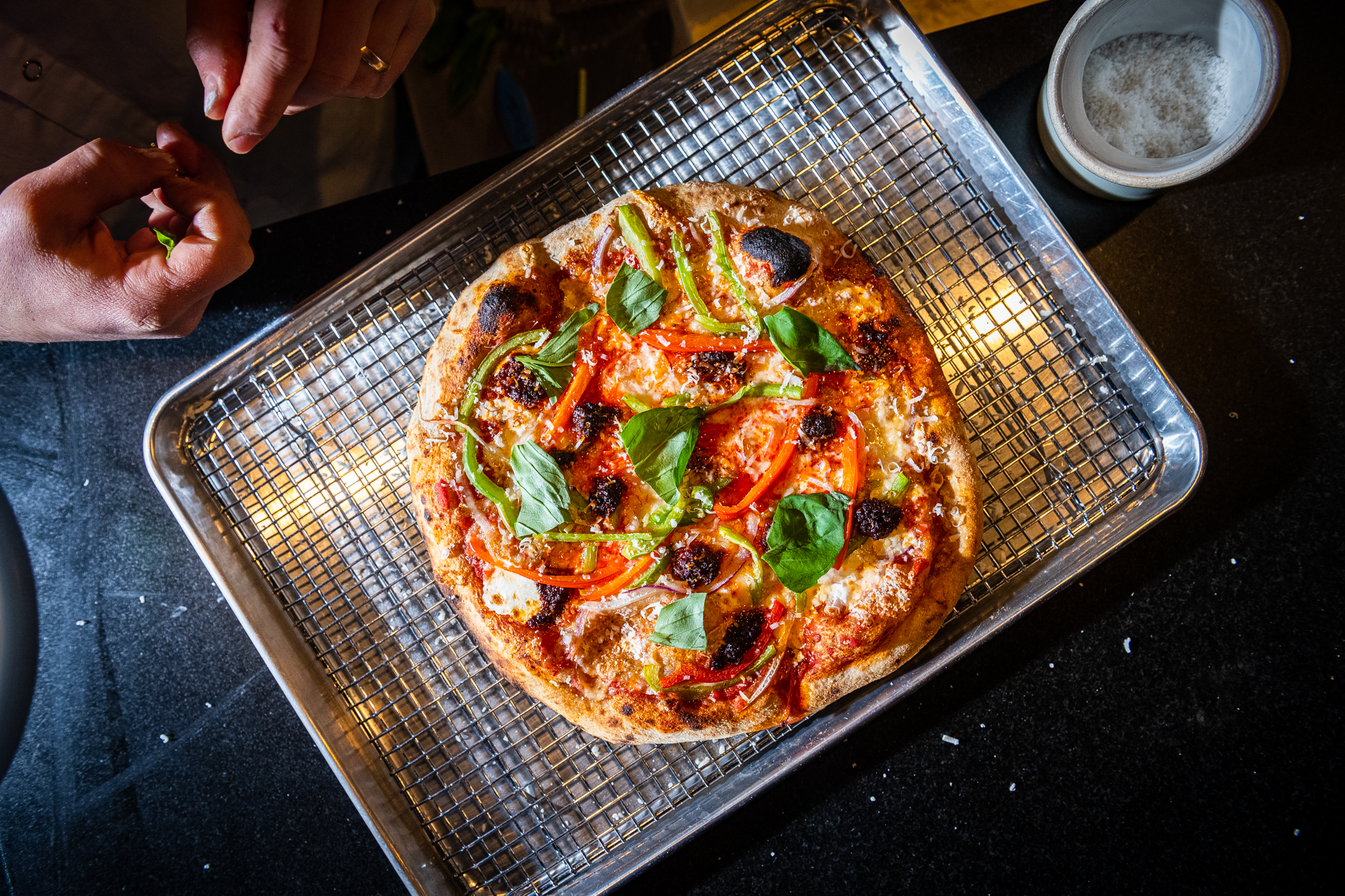 """Martha Dear's """"Sausage + Peppers"""" sourdough pizza with tomato, mozzarella, onions, peppers, and 'nduja sausage."""