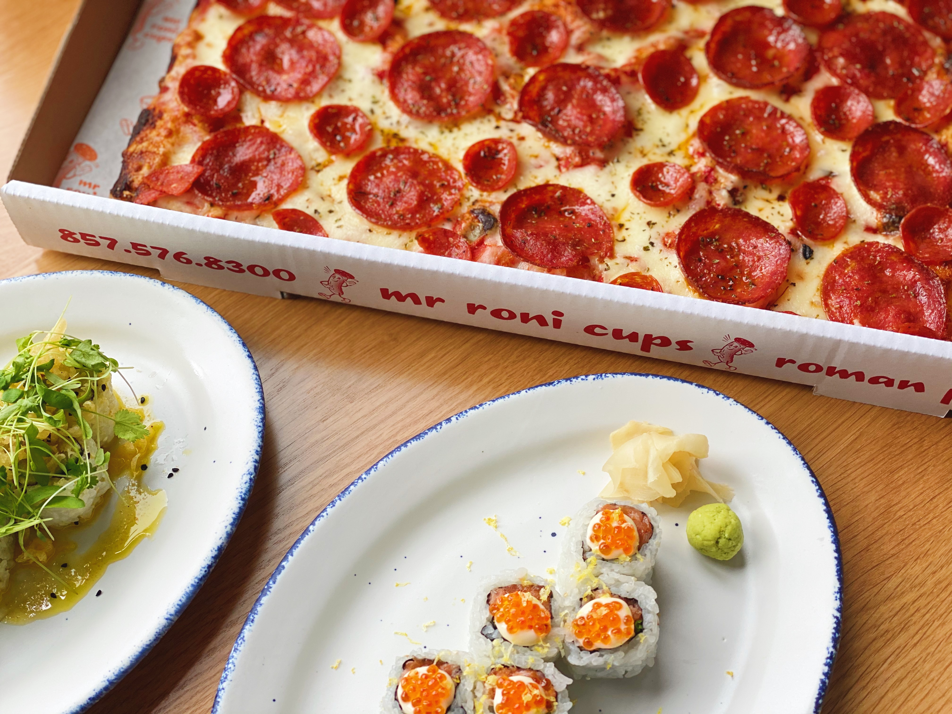 A salad, sushi roll, and pepperoni pizza situaded side by side on a wooden table