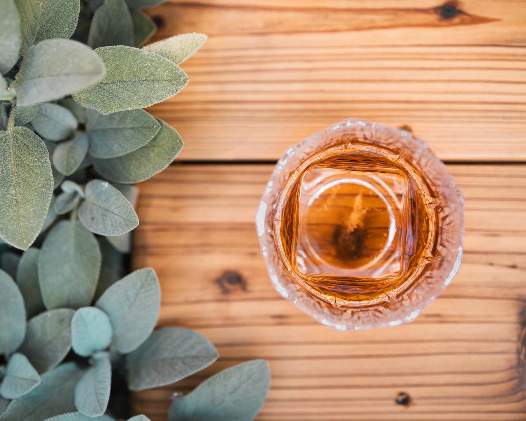 A glass of whisky sits on a wooden table outside Scotch Lodge
