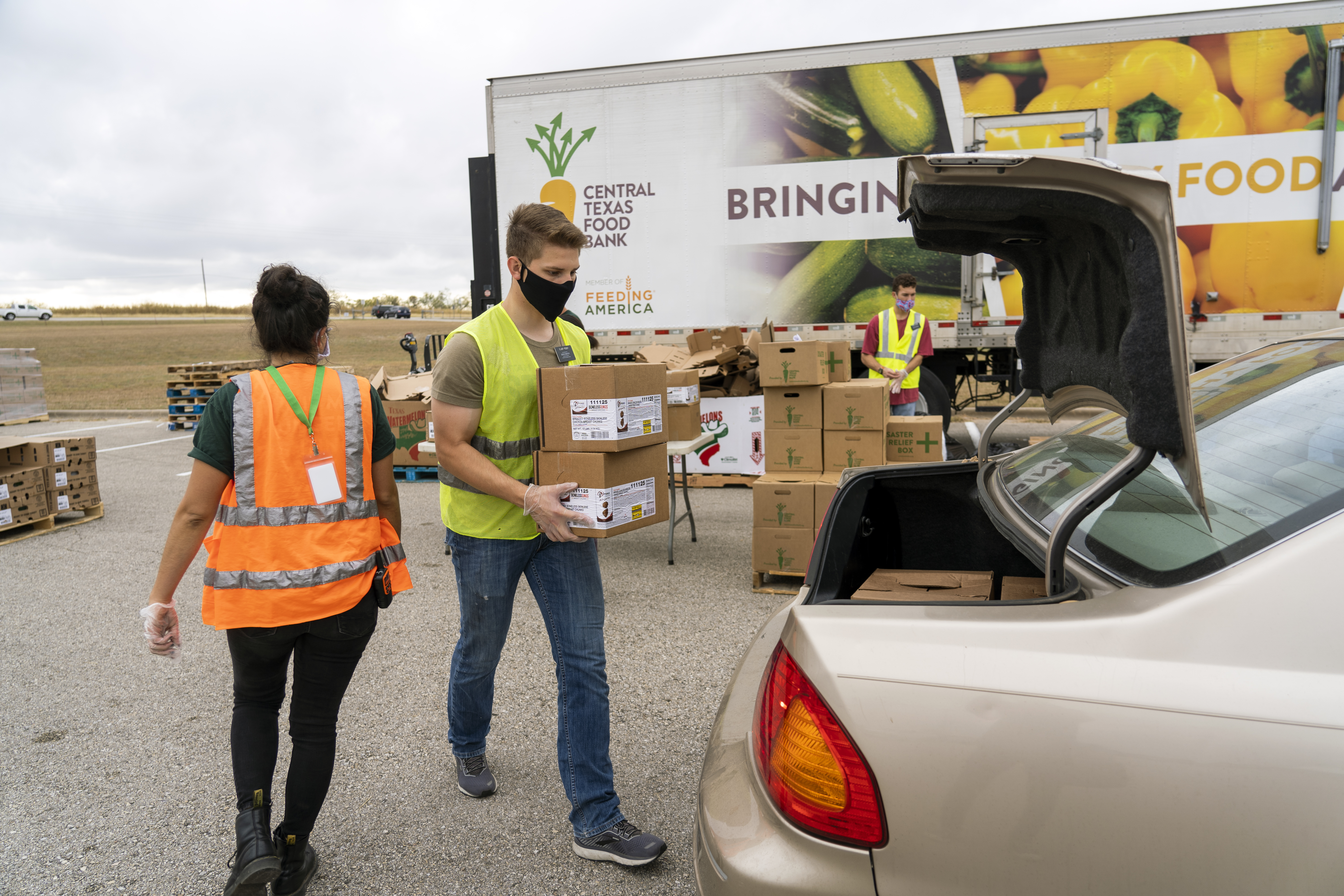 People load boxes of food off a large truck and into the open trunk of a car.