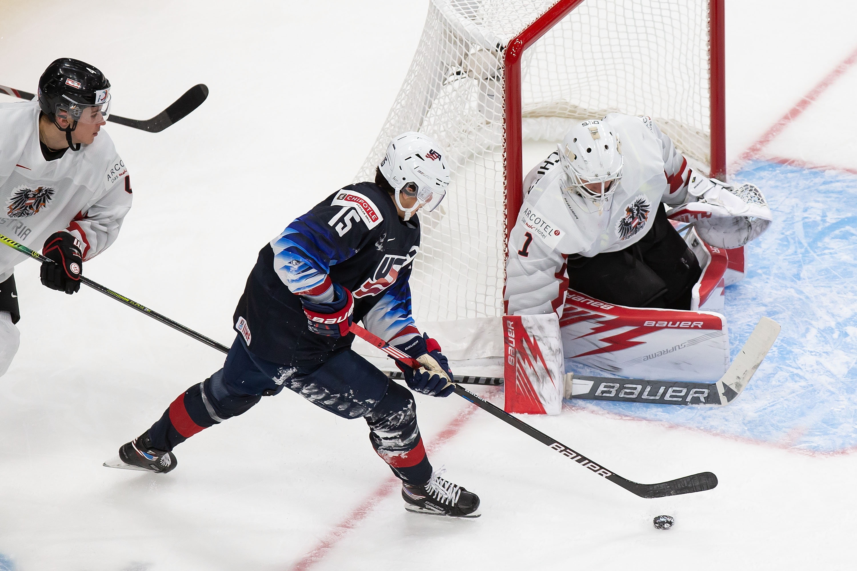 Alex Turcotte #15 of the United States looks for a shot against goaltender Sebastian Wraneschitz #1 of Austria during the 2021 IIHF World Junior Championship at Rogers Place on December 26, 2020 in Edmonton, Canada.