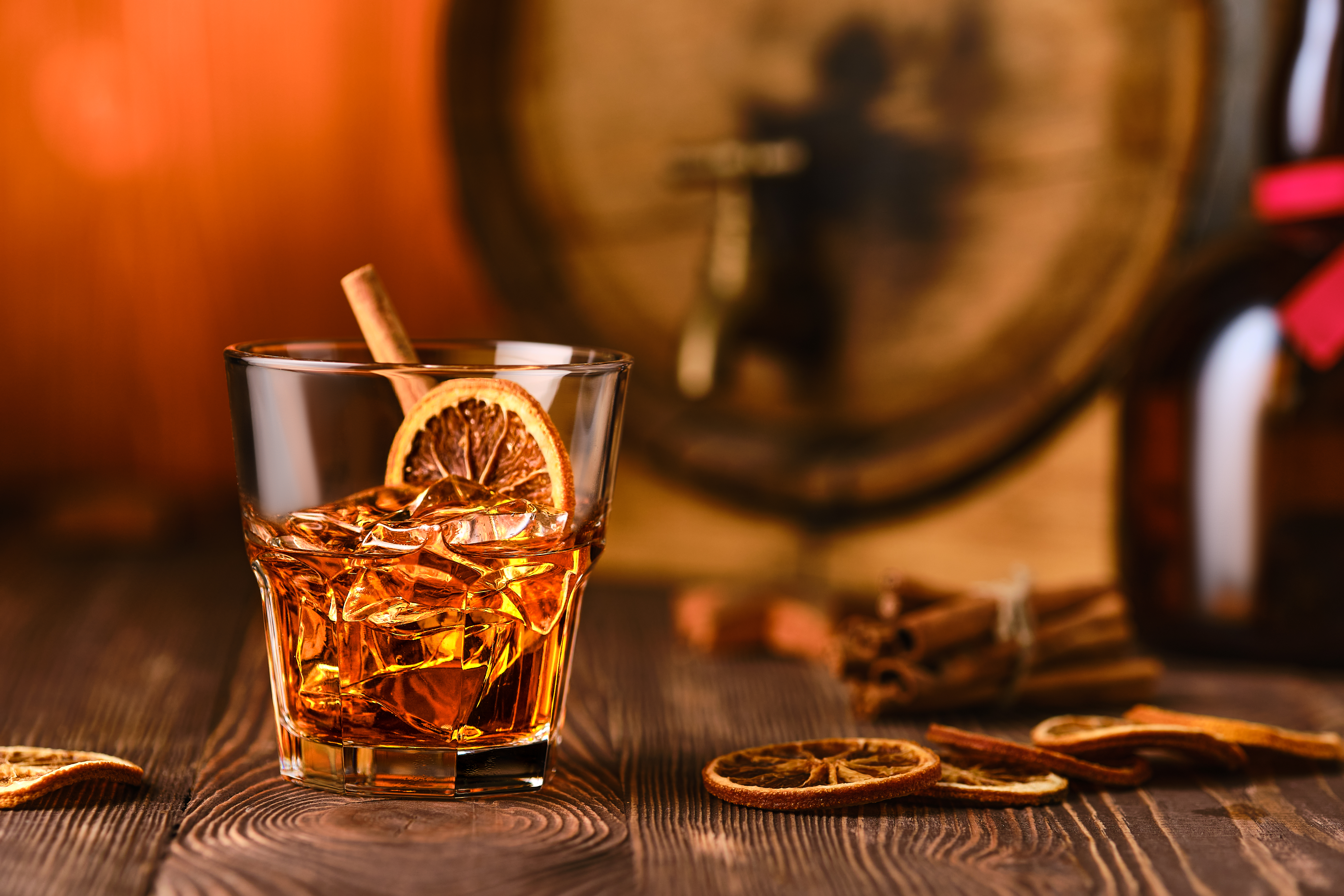 Glass of cocktail with whisky and orange liquor with barrel on background.