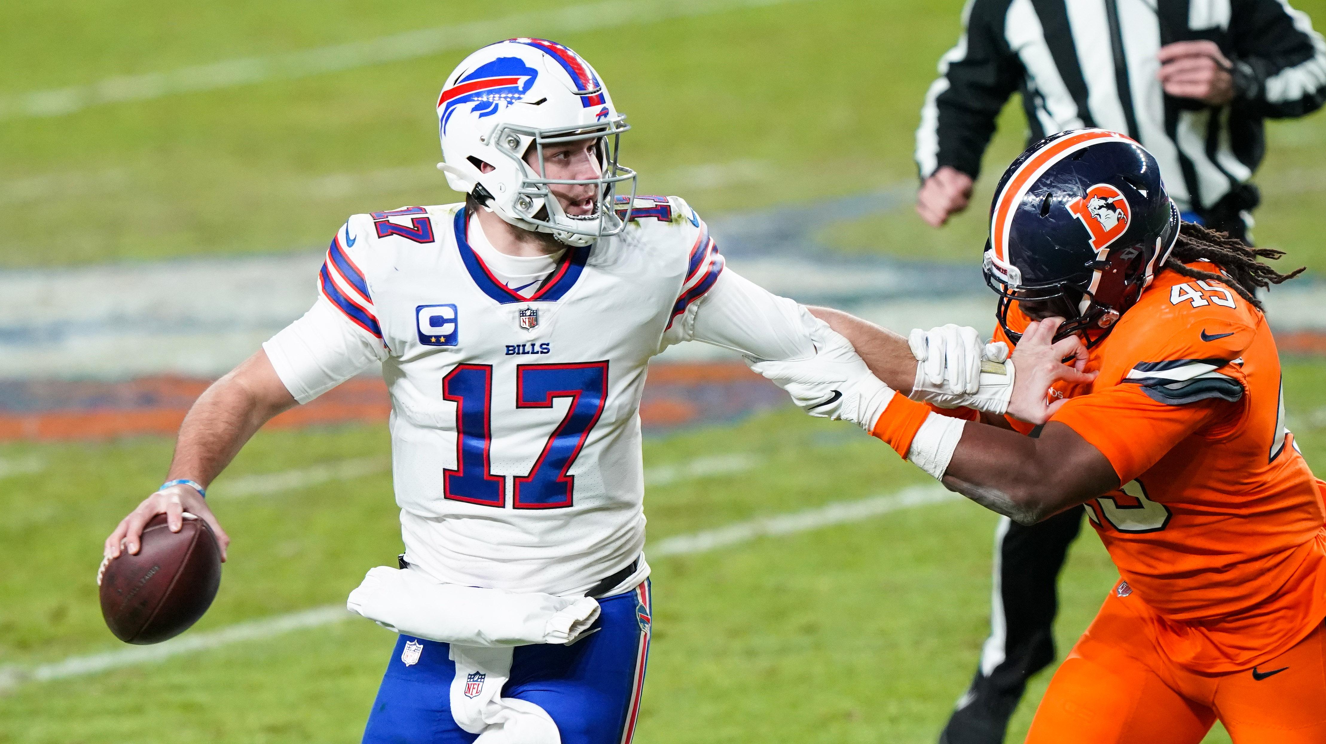 Buffalo Bills quarterback Josh Allen (17) stiff arms Denver Broncos linebacker A.J. Johnson (45) during the third quarter at Empower Field at Mile High.