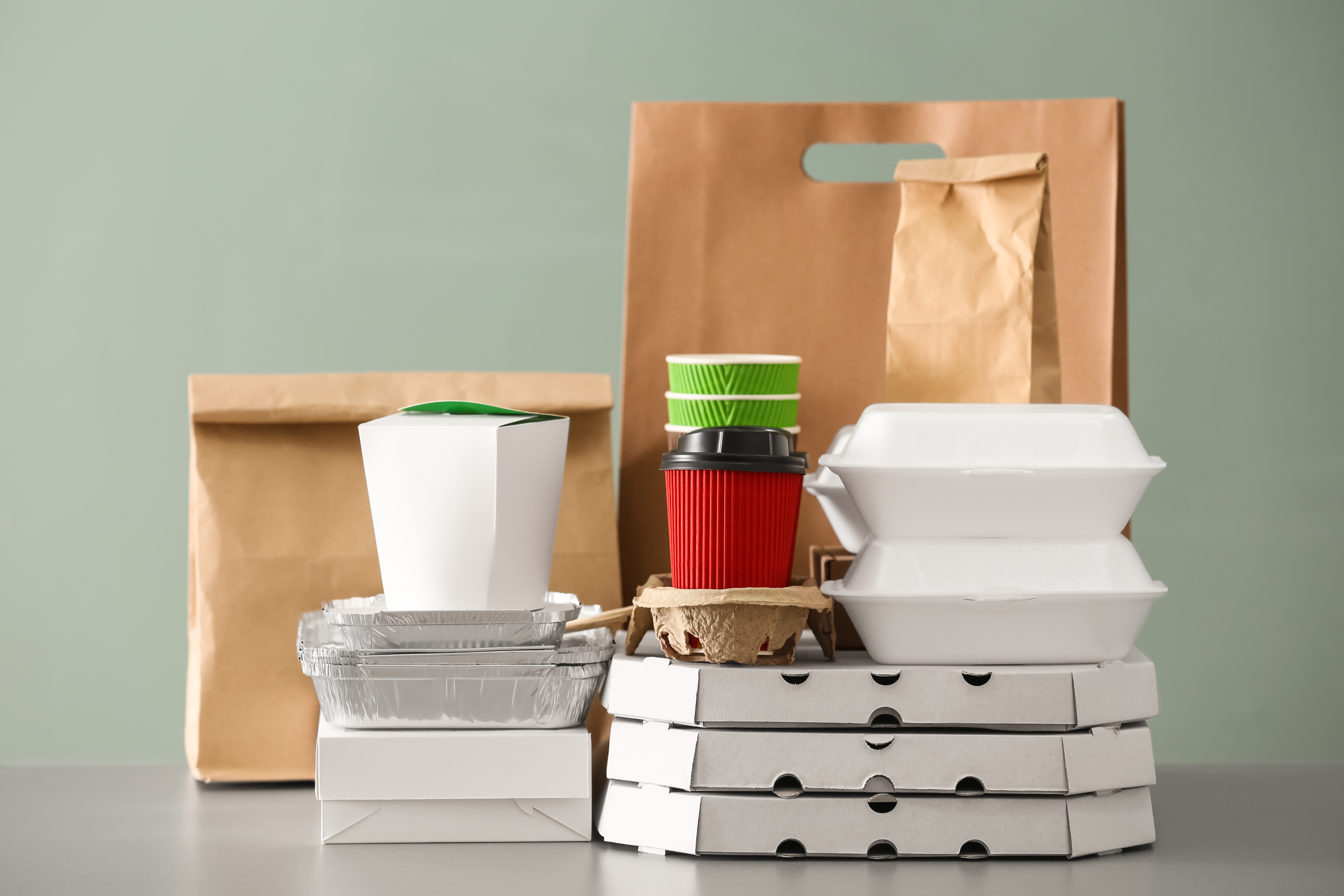 A display showing various takeout boxes, cups, and bags against a blank background