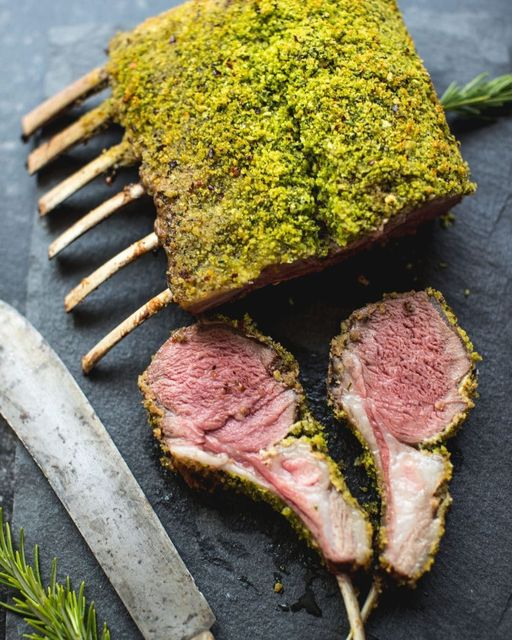 A whole rack of lamb is encrusted with herby breadcrumbs with two slices showing a glorious medium rare interior