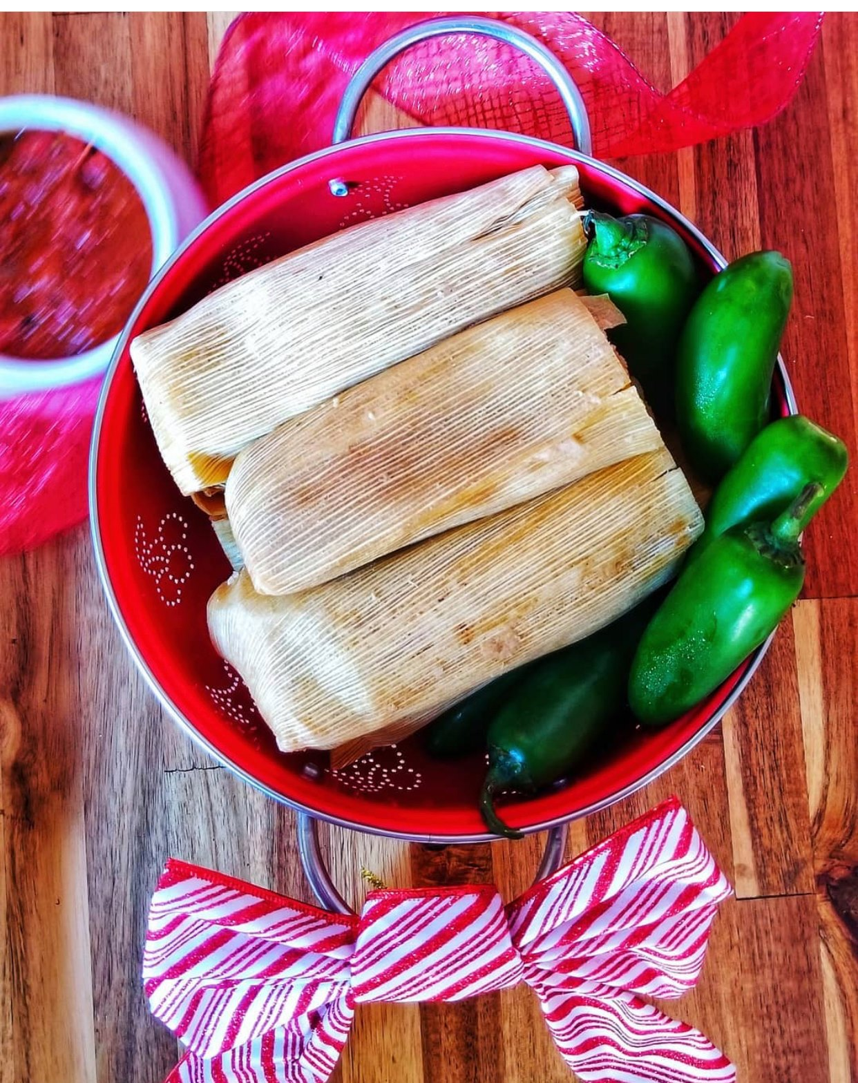 Three tamales in a red bowl with green peppers