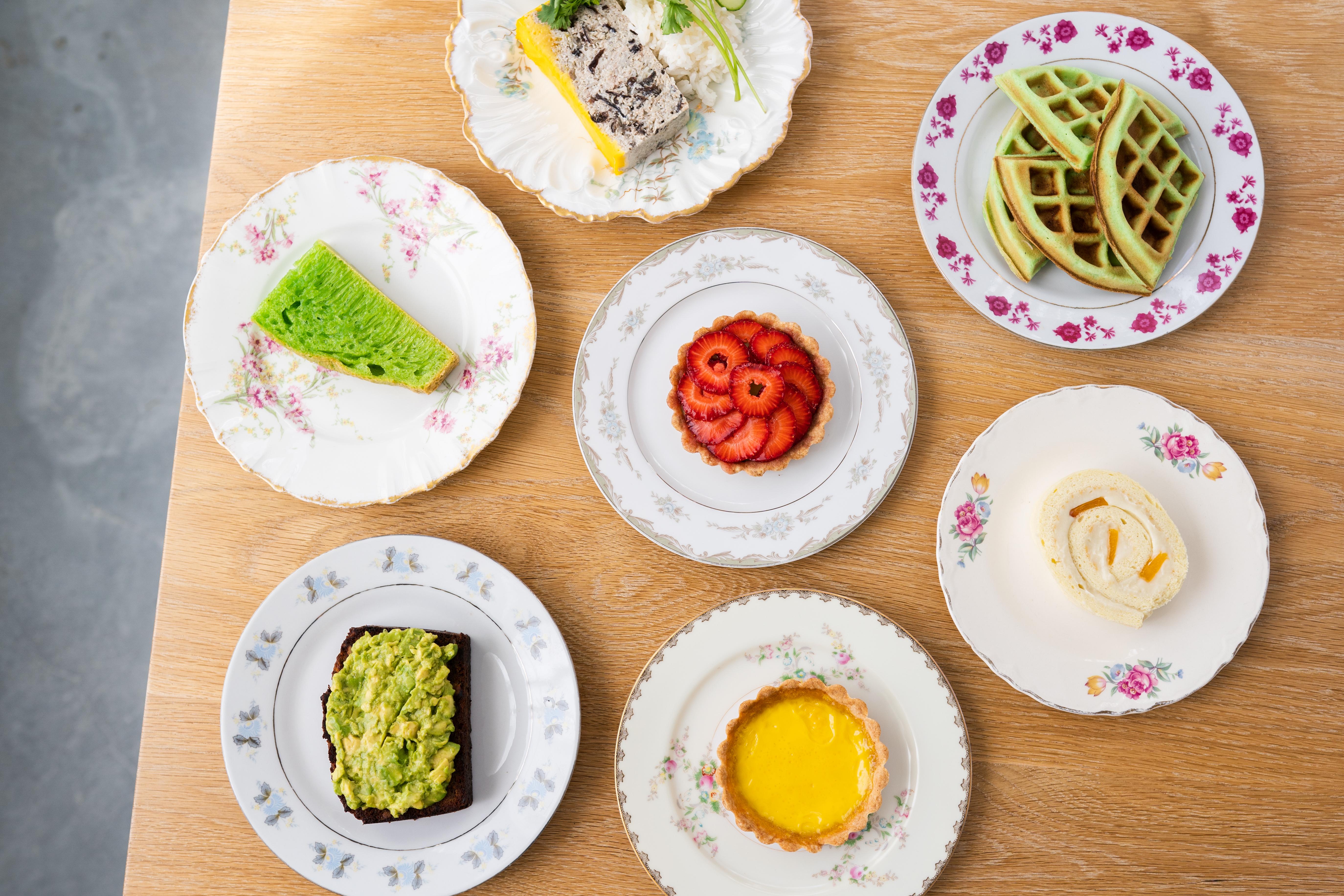 On a wooden table, Berlu's Vietnamese pastries sit on little plates. They range from fruit tarts to pandan waffles to mango roulades.