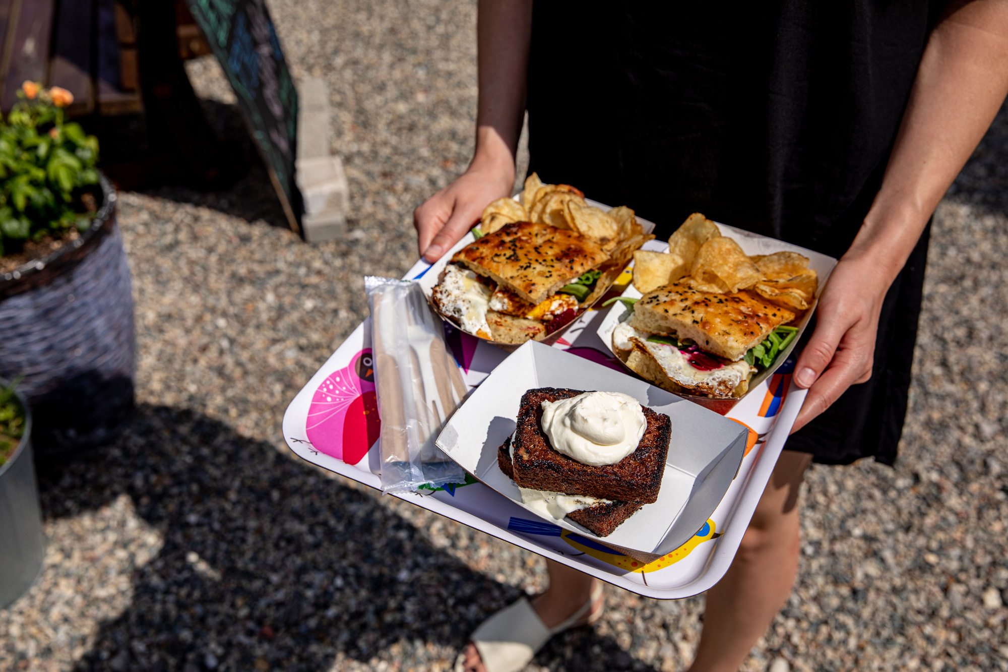 A platter with two sandwiches and dessert bread in the hands of a woman with a black dress and white slip on shoes.