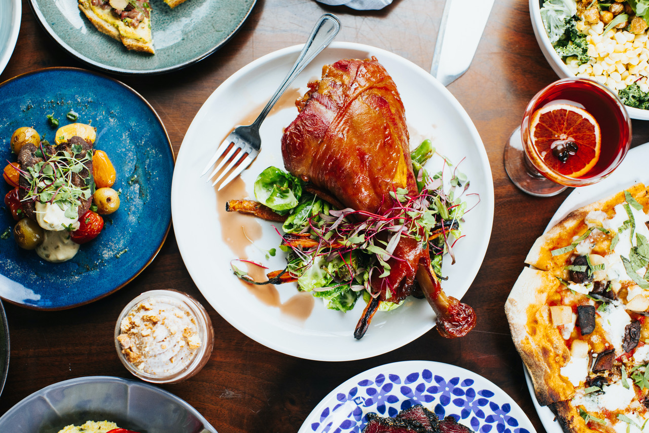 an overhead show of several dishes, the central is which is a large turkey leg on a bed of greens
