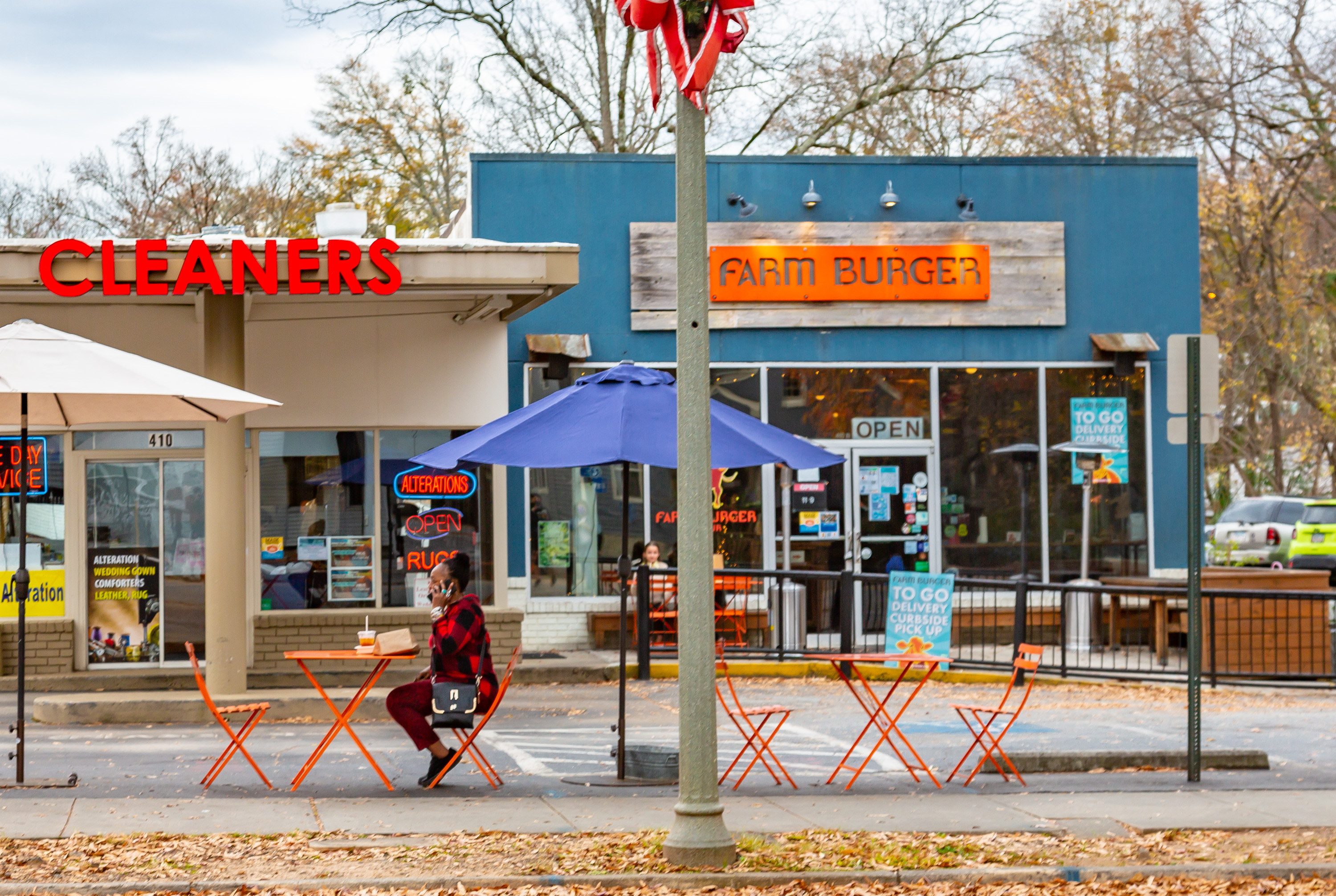 A woman dressed in a red plaid sweater and red leggings with black flats sits at an orange metal table in front of Farm Burger in Decatur, Georgia, on a December 2020 afternoon talking on the phone and eating a burger and fries