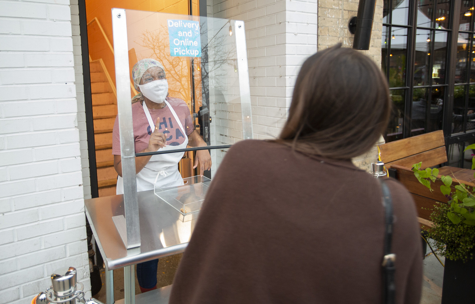 A restaurant worker wearing a mask taking an order through plexiglas.