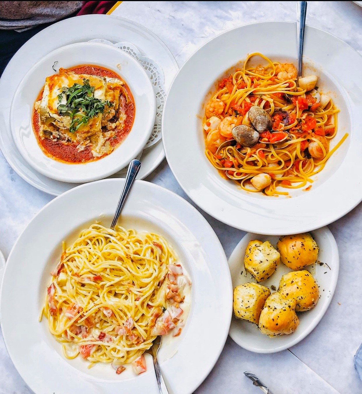 Four white plates hold classic Italian food including seafood pasta and garlic knots.