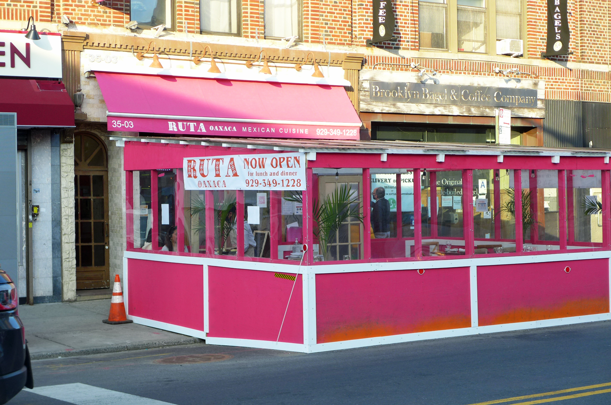 A dark pink awning and an outdoor dining enclosure in front in the same shade.