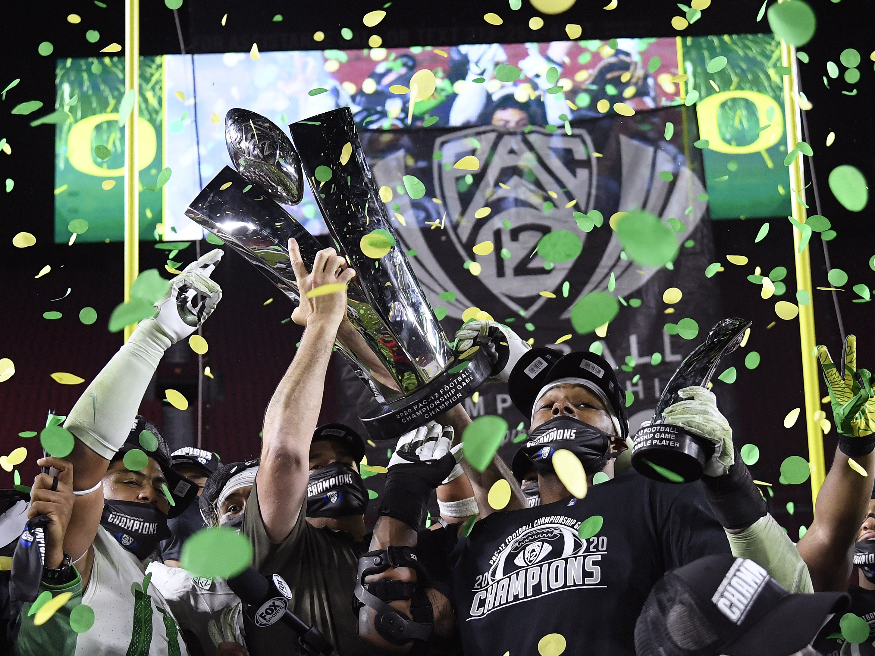 Head coach Mario Cristobal hoists the trophy, with most valuable player, Kayvon Thibodeaux of the Oregon Ducks, in celebration a 31-24 win over the USC Trojans during the PAC 12 2020 Football Championship at United Airlines Field at the Coliseum on December 18, 2020 in Los Angeles, California.
