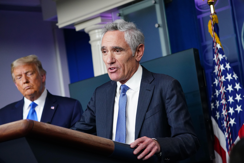 President Donald Trump listens to White House coronavirus adviser Scott Atlas speak from a podium during a press conference in the White House on September 23, 2020.