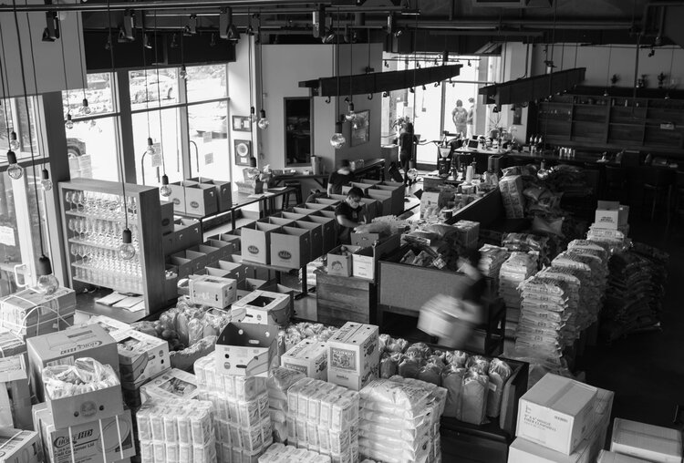 Black and white photograph of a restaurant interior packed with huge stacks of boxes full of groceries