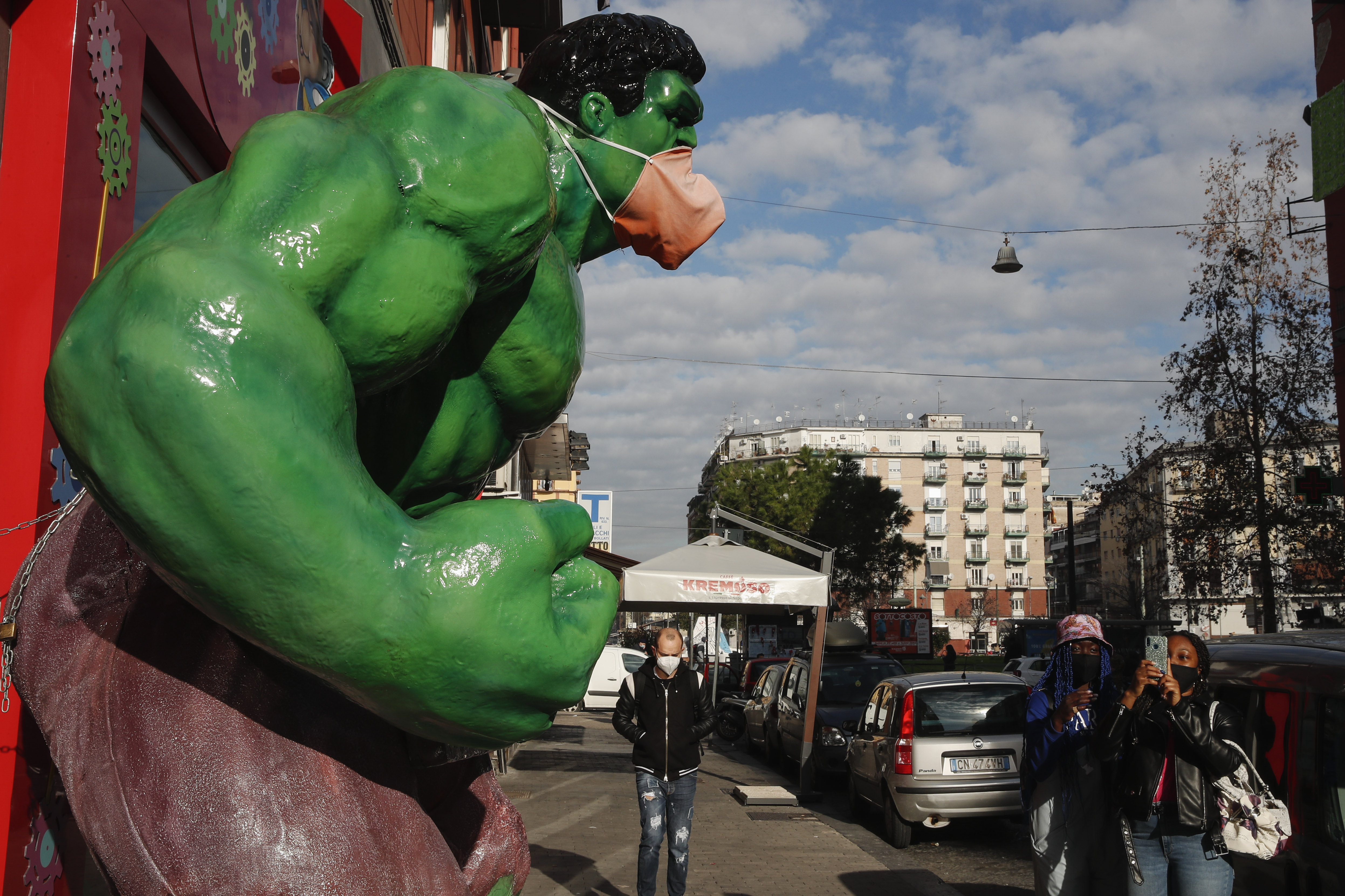 Tourist takes a photo to a figure of Marvel Comics character...