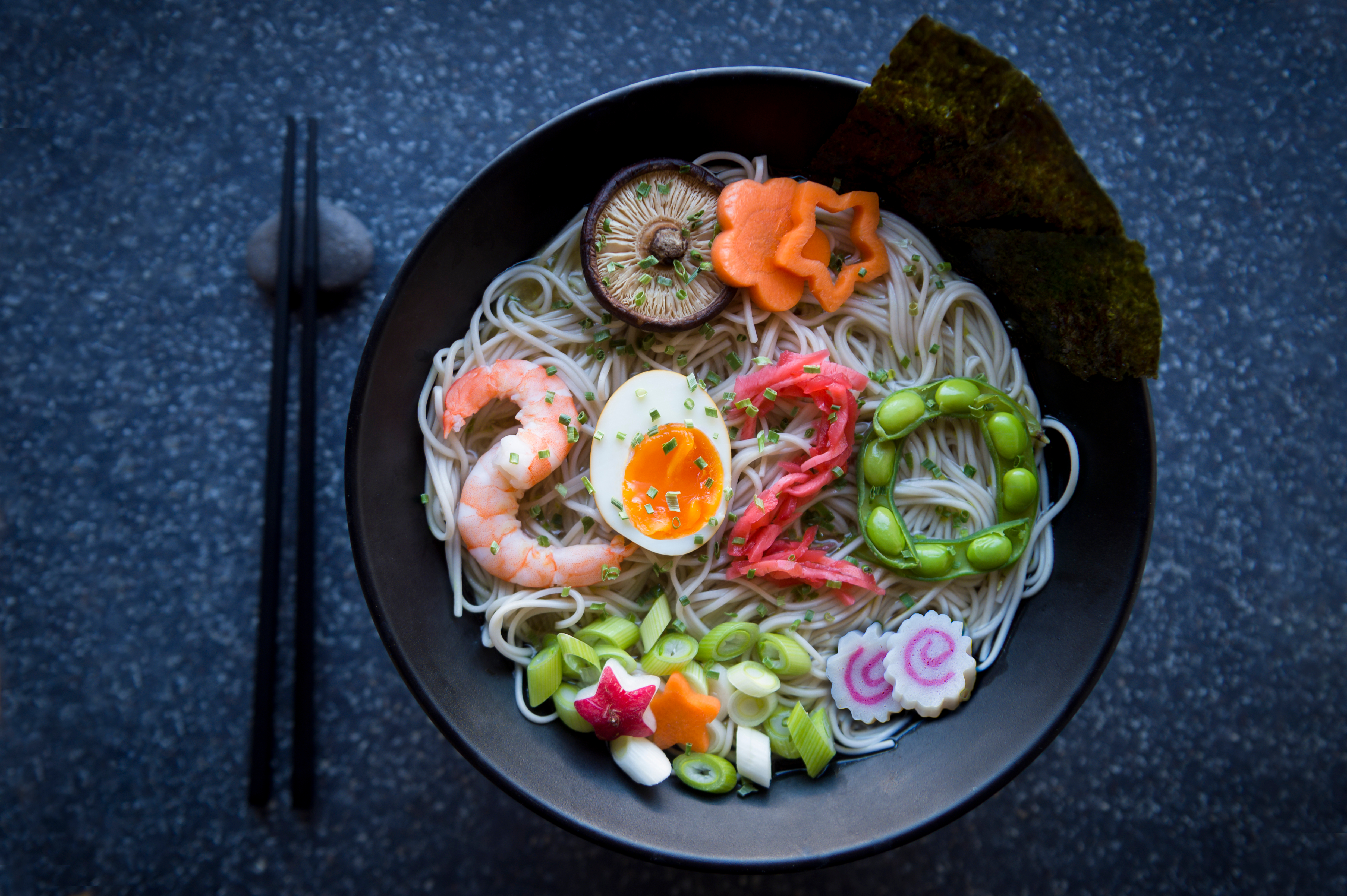 Bowl of Japanese buckwheat ramen noodle soup topped with the number 2020 spelled out of shrimp, boiled egg, pickled ginger, and edamame beans