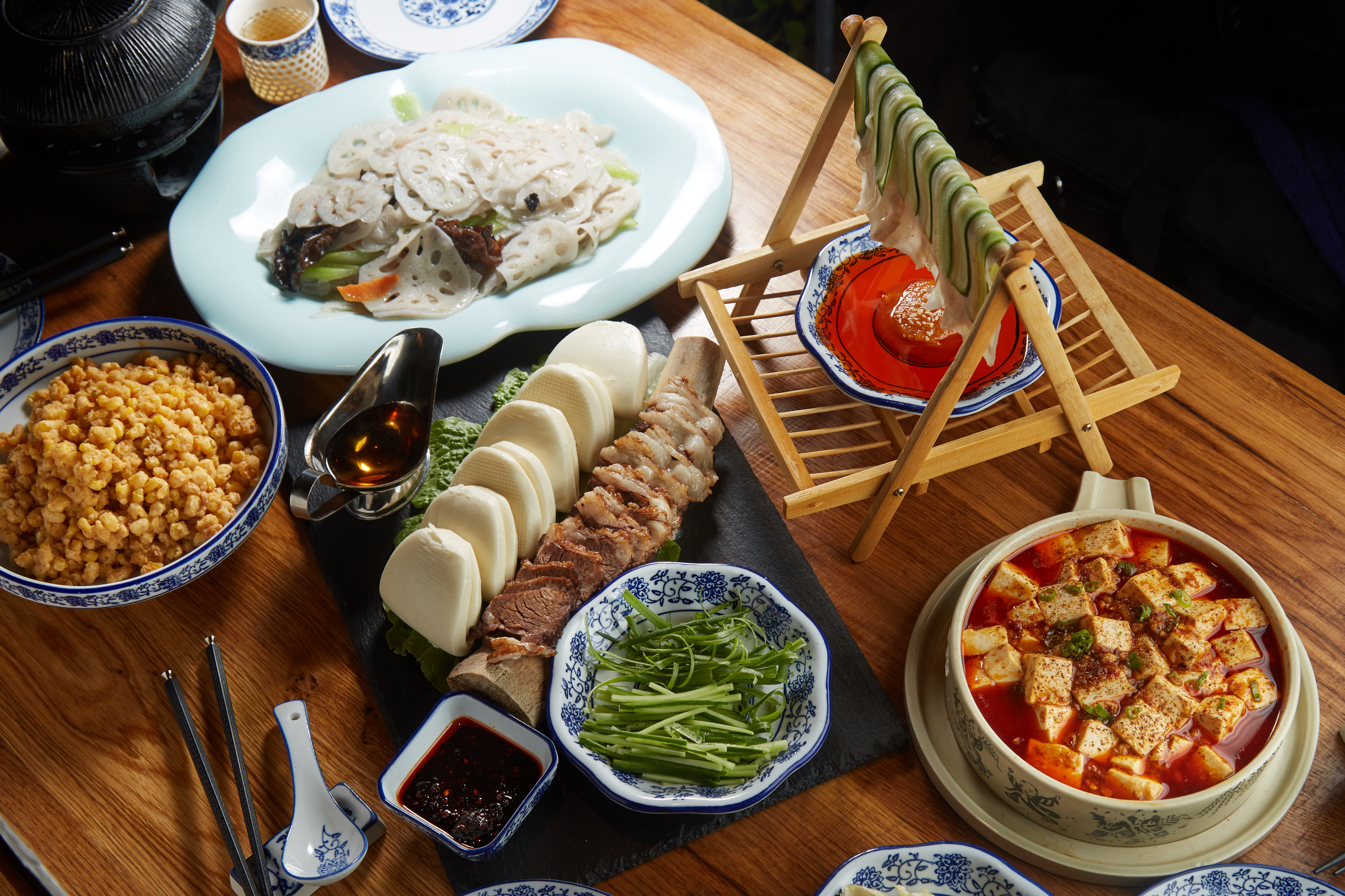 A selection of Sichuan dishes, including thinly sliced cucumber, mapo tofu, and lotus root