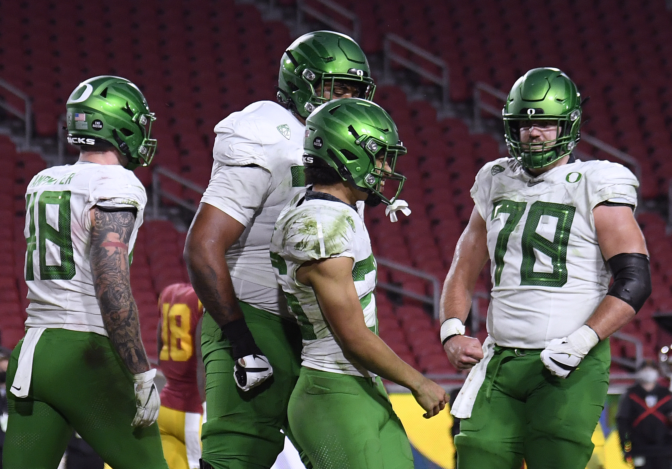 Travis Dye #26 of the Oregon Ducks celebrates his touchdown with Hunter Kampmoyer #48, Steven Jones #74 and Alex Forsyth #78, to take a 31-21 lead over the USC Trojans, during the third quarter in the PAC 12 2020 Football Championship at United Airlines Field at the Coliseum on December 18, 2020 in Los Angeles, California.