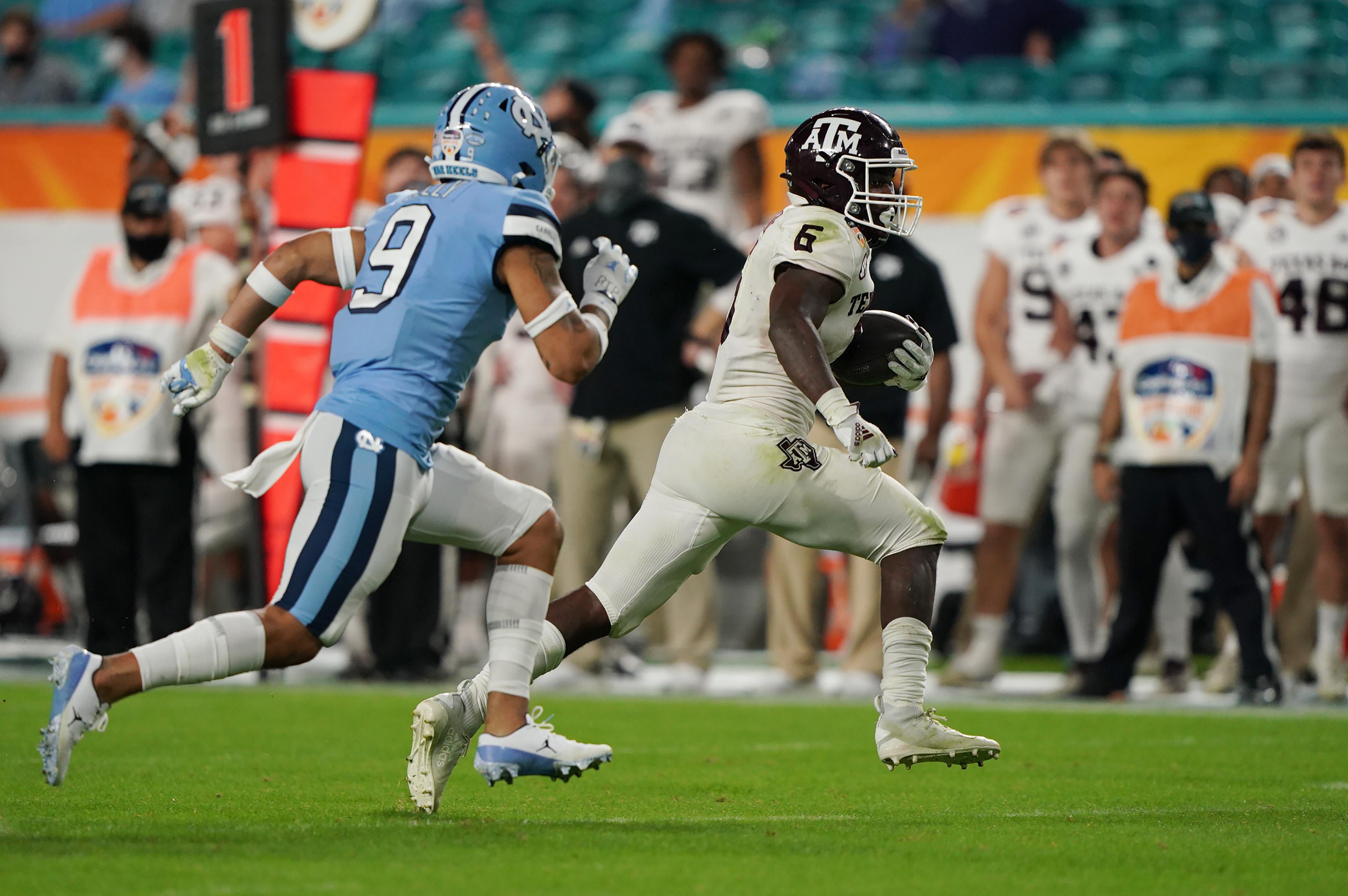 Texas A&M Aggies running back Devon Achane runs past North Carolina Tar Heels defensive back Cam'Ron Kelly for a 76-yard touchdown during the second half at Hard Rock Stadium.