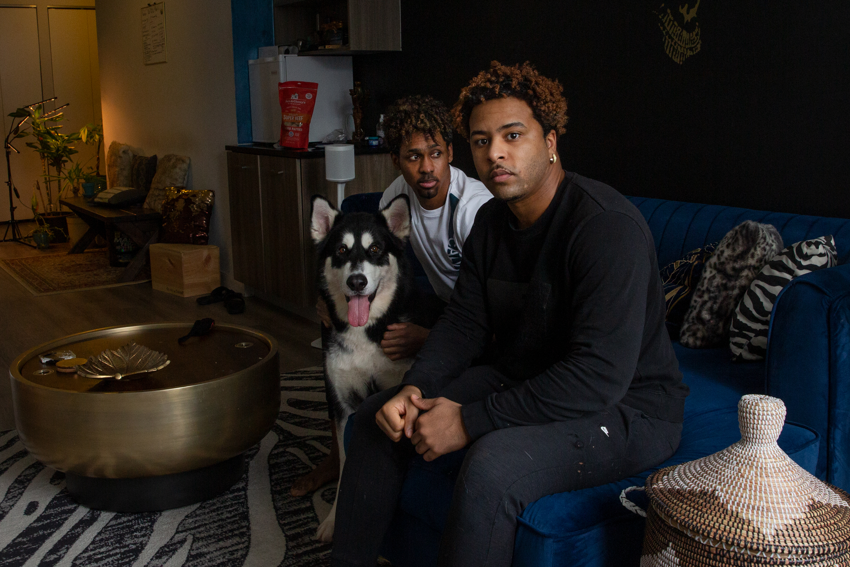 Roommates Nikko Lester, right, and Stephan Nylon Bartholomew, with their Alaskan husky Onyx, Dec. 18, 2020.