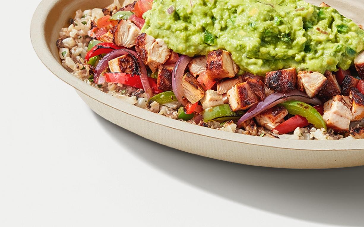 A Chipotle burrito bowl with cauliflower rice, chicken, fajita veggies, guacamole, and more.
