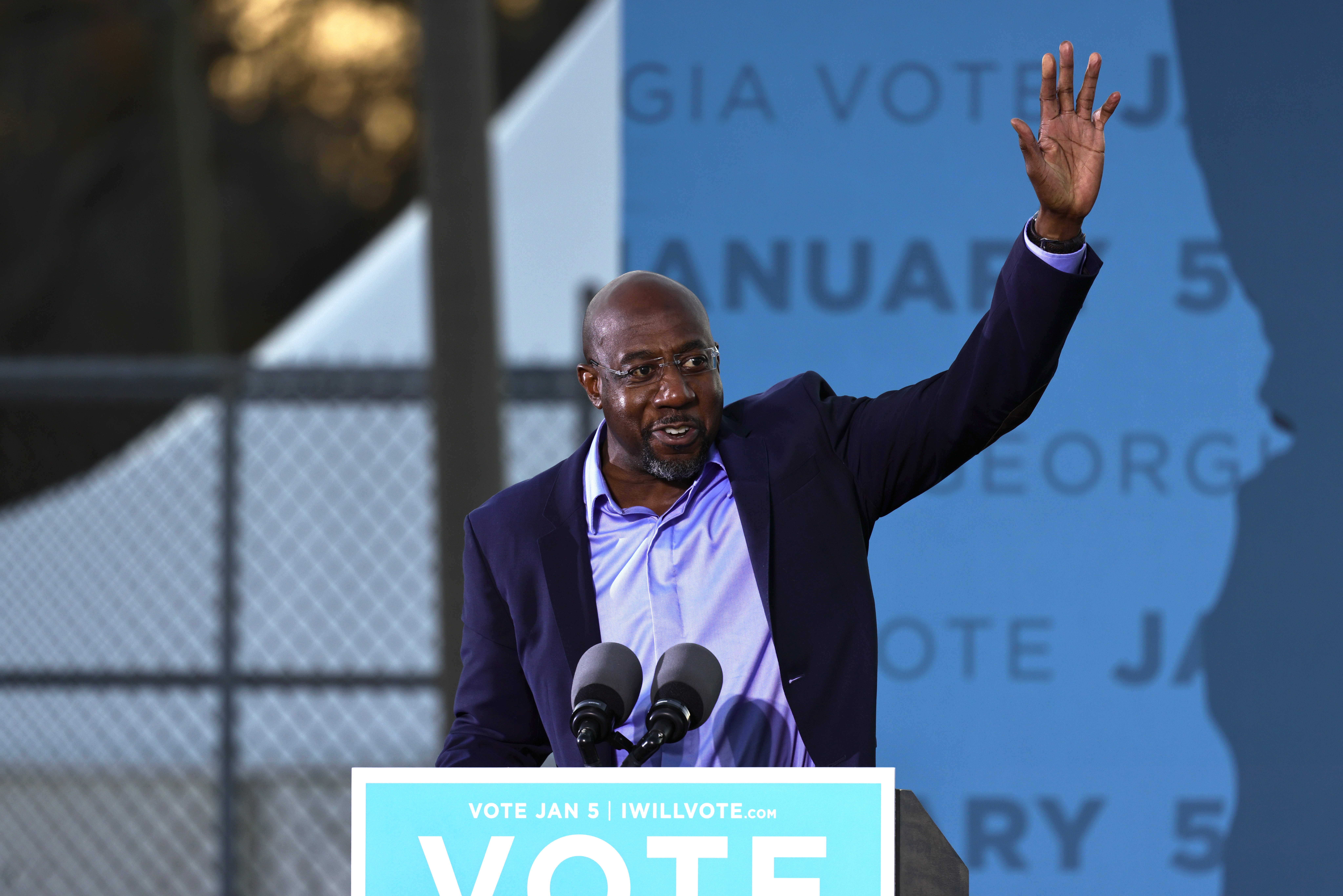 Georgia Democratic Senate candidate Rev. Raphael Warnock waves after finishing his speech during a drive-in rally at Garden City Stadium on January 03, 2021 in Savannah, Georgia.