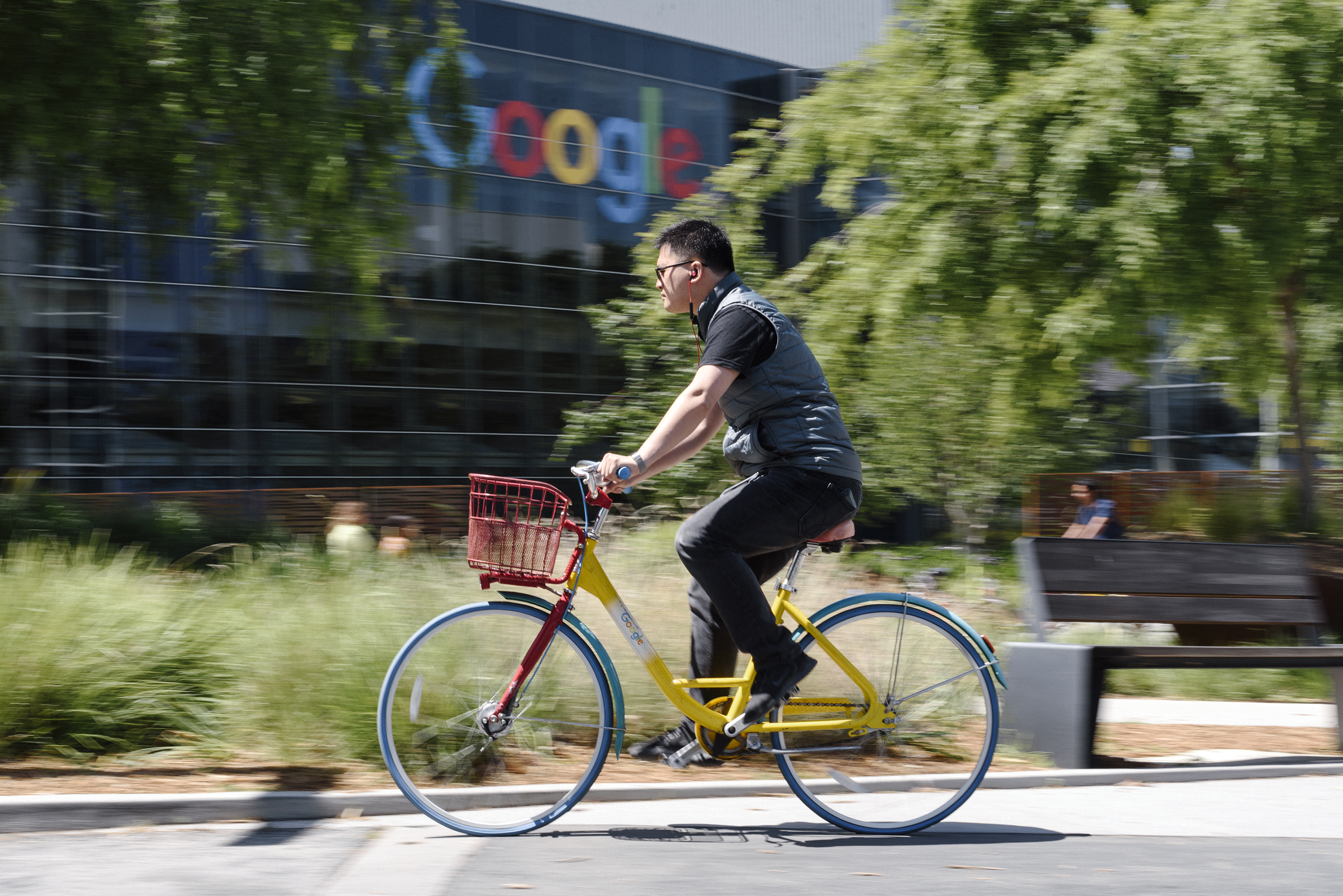 A person rides a bike past signage on the Google campus.