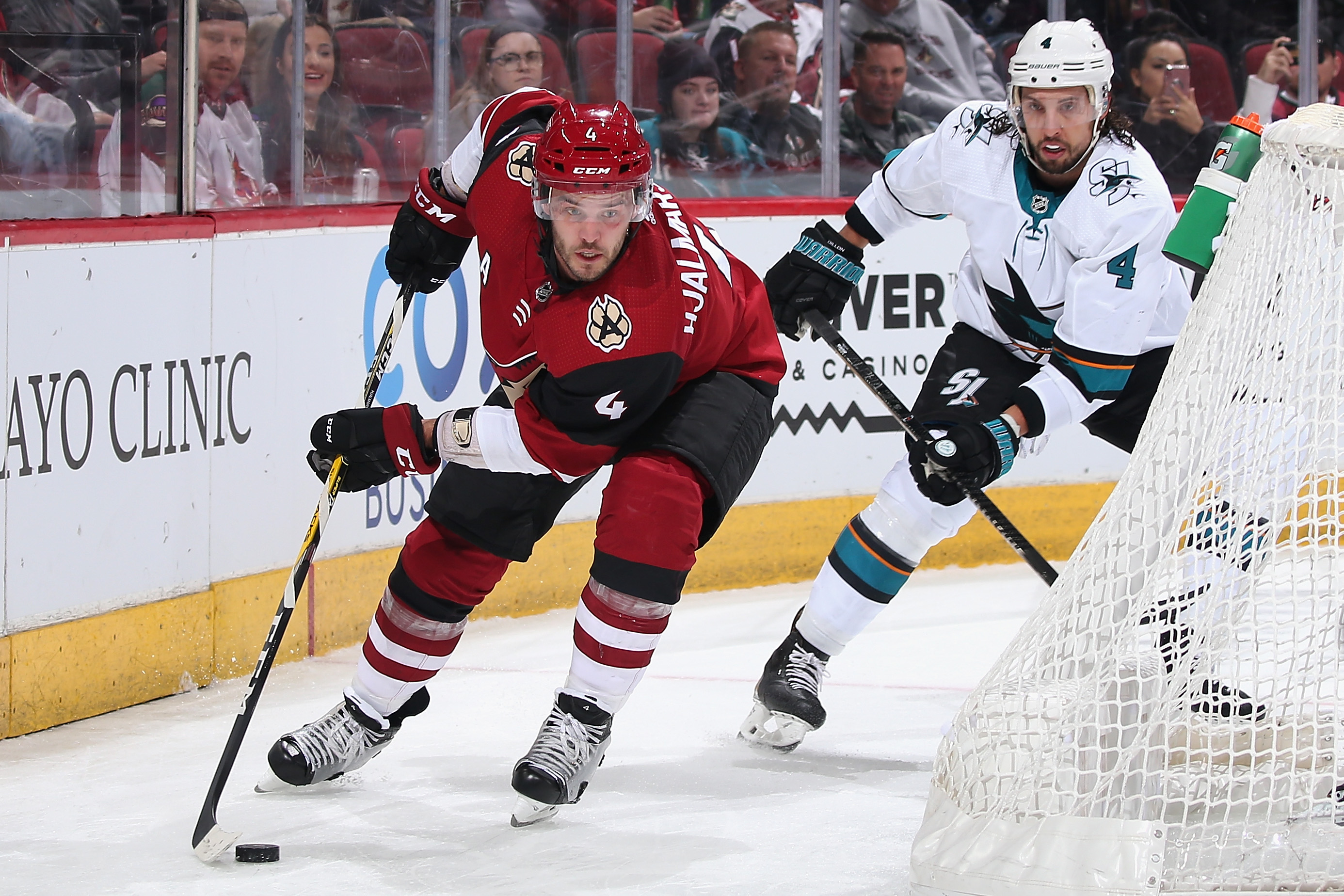 Niklas Hjalmarsson #4 of the Arizona Coyotes skates with the puck ahead of Brenden Dillon #4 of the San Jose Sharks during the first period of the NHL game at Gila River Arena on January 14, 2020 in Glendale, Arizona.