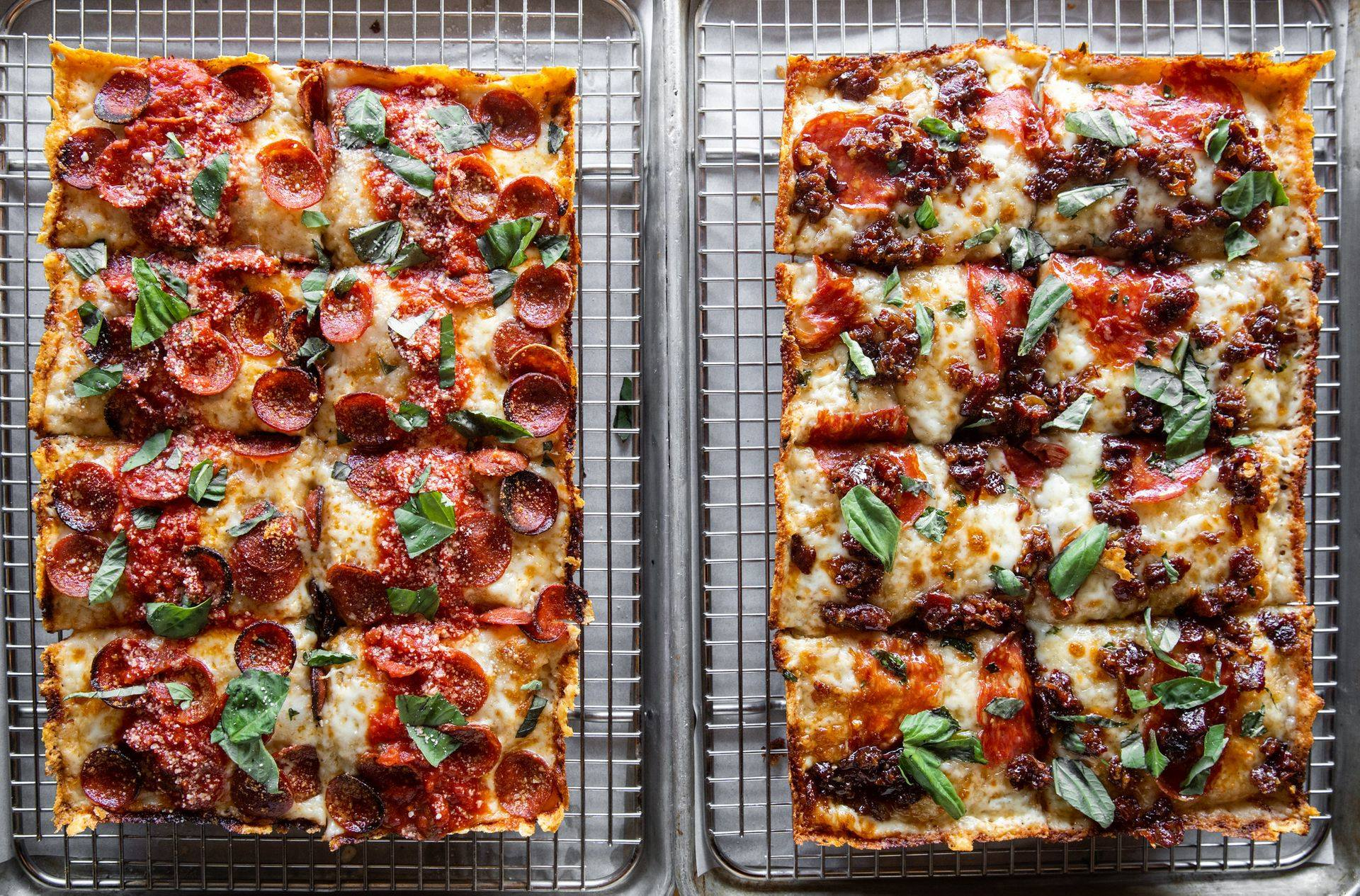 Two Detroit-style pizzas cooling on wire racks side by side