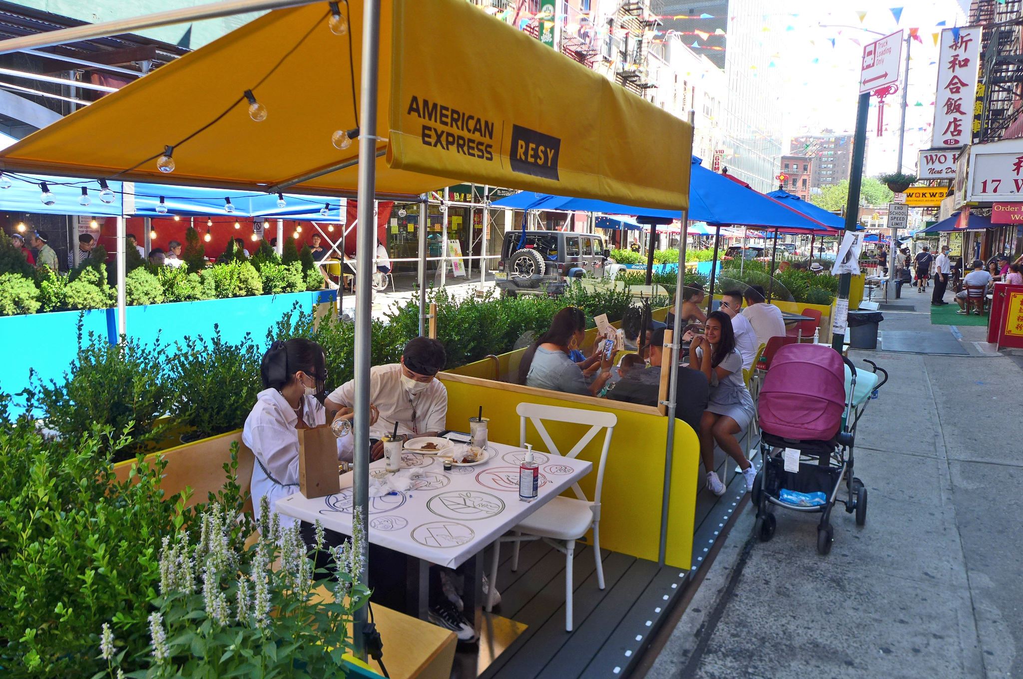 An outddor table with an awning surrounded by flowers.