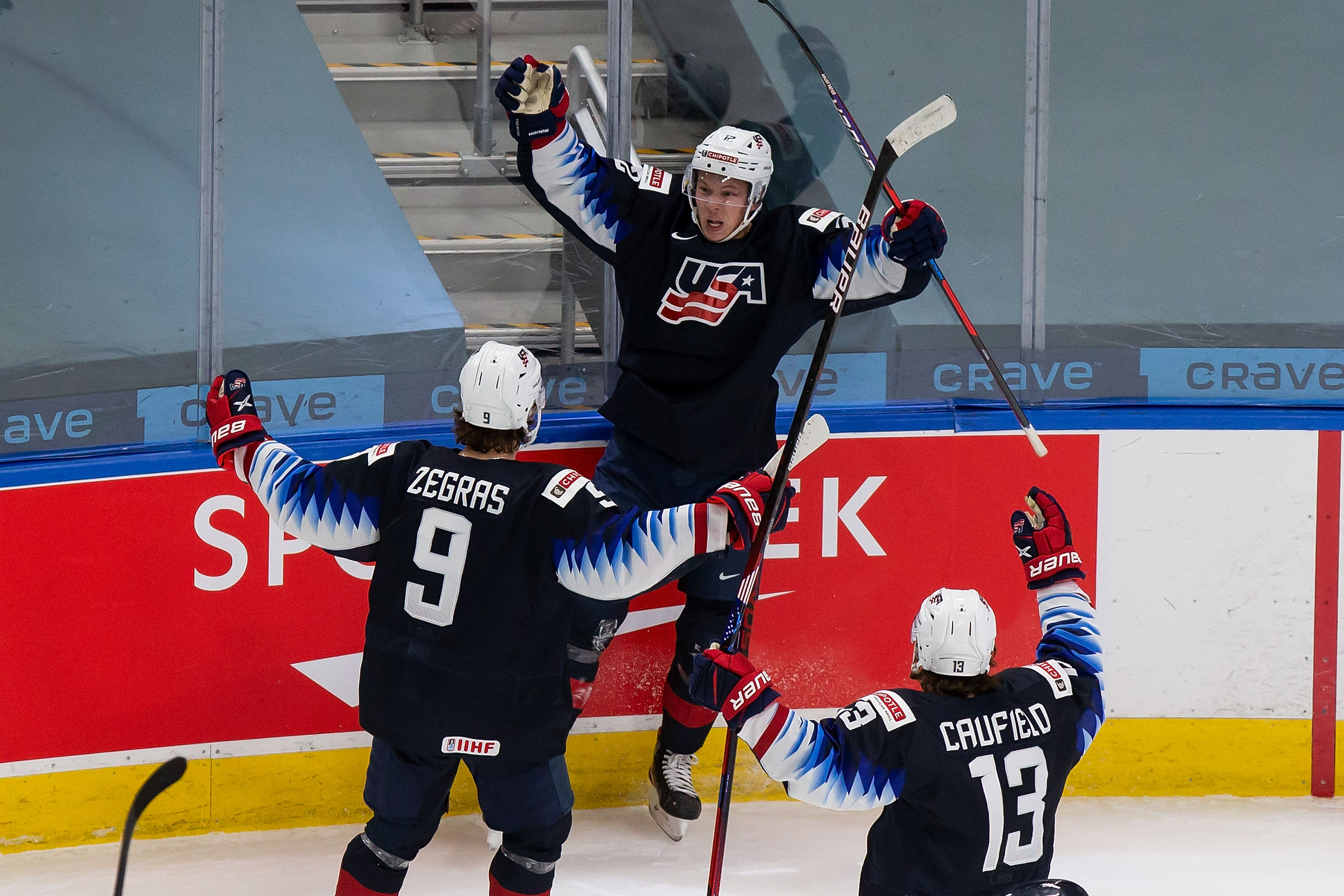 Trevor Zegras #9, Matthew Boldy #12 and Cole Caulfield #13 of the United States celebrate a goal against Finland during the 2021 IIHF World Junior Championship semifinals at Rogers Place on January 4, 2021 in Edmonton, Canada.