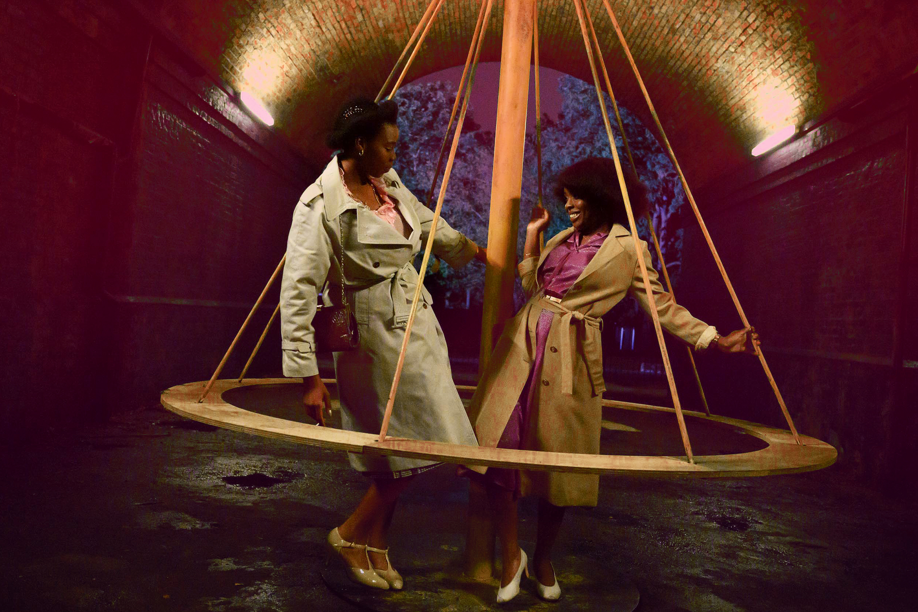 Two women stand inside a large spinning top