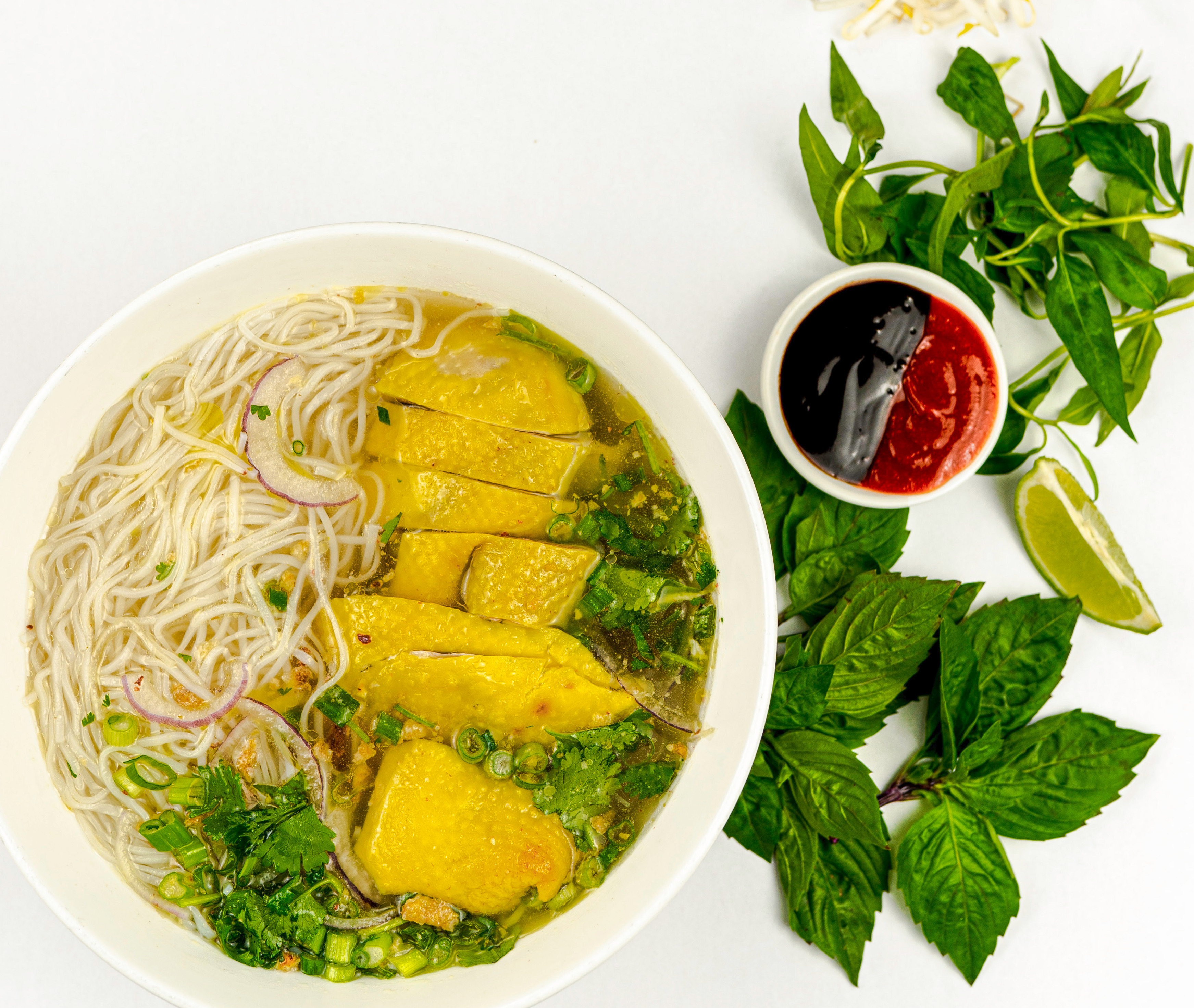A bowl of noodle soup is topped with chicken, next to an assortment of mint, basil, hoisin, sriracha, and limes