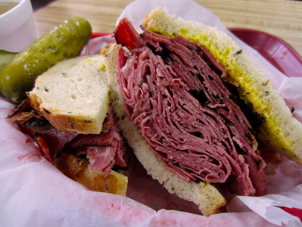 A stack of pastrami inside a sandwich with lots of mustard.