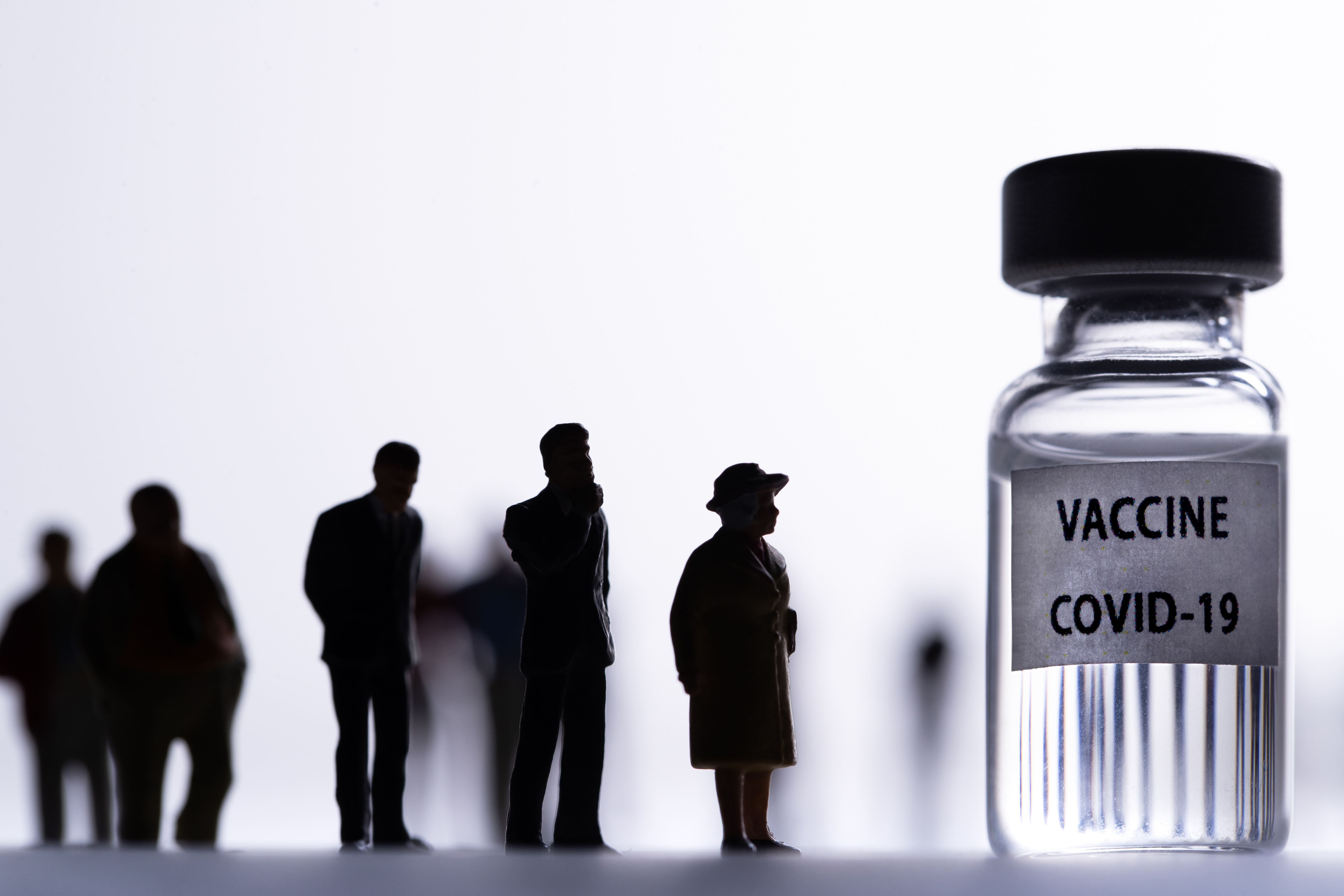 "Silhouetted people lining up in front of a medical vial labeled ""vaccine Covid-19."""