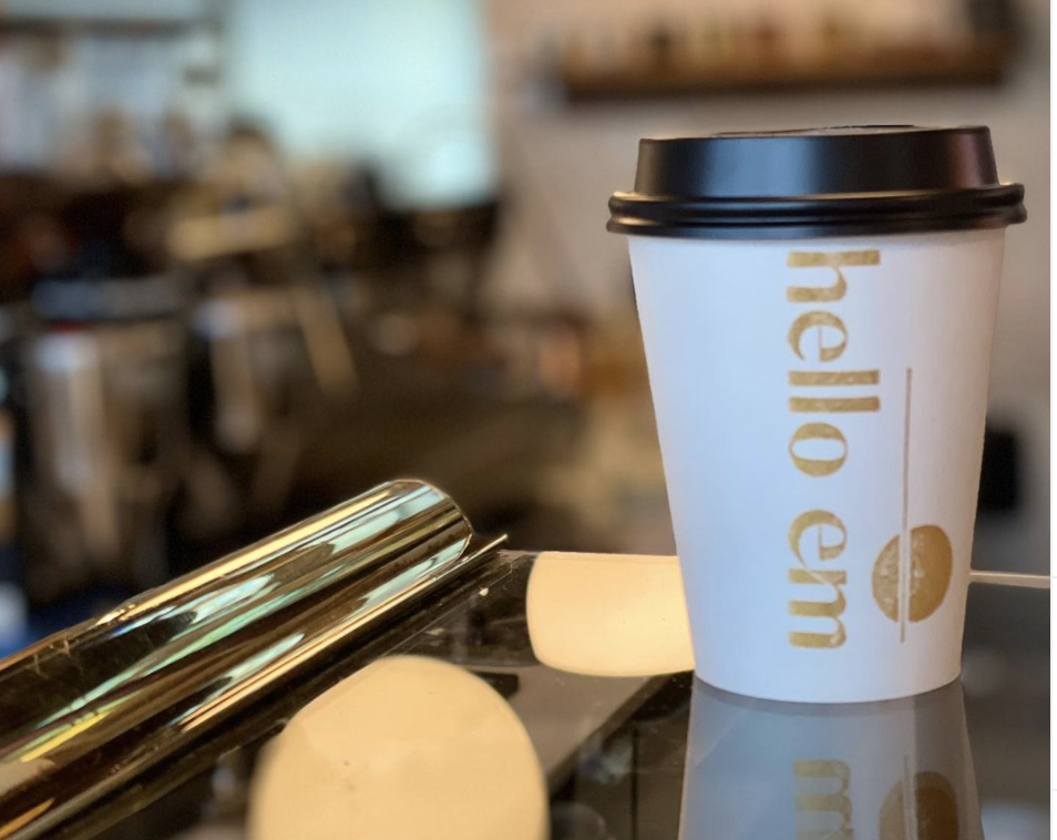 """A paper cup that says """"Hello Em"""" in gold lettering on a cafe counter"""