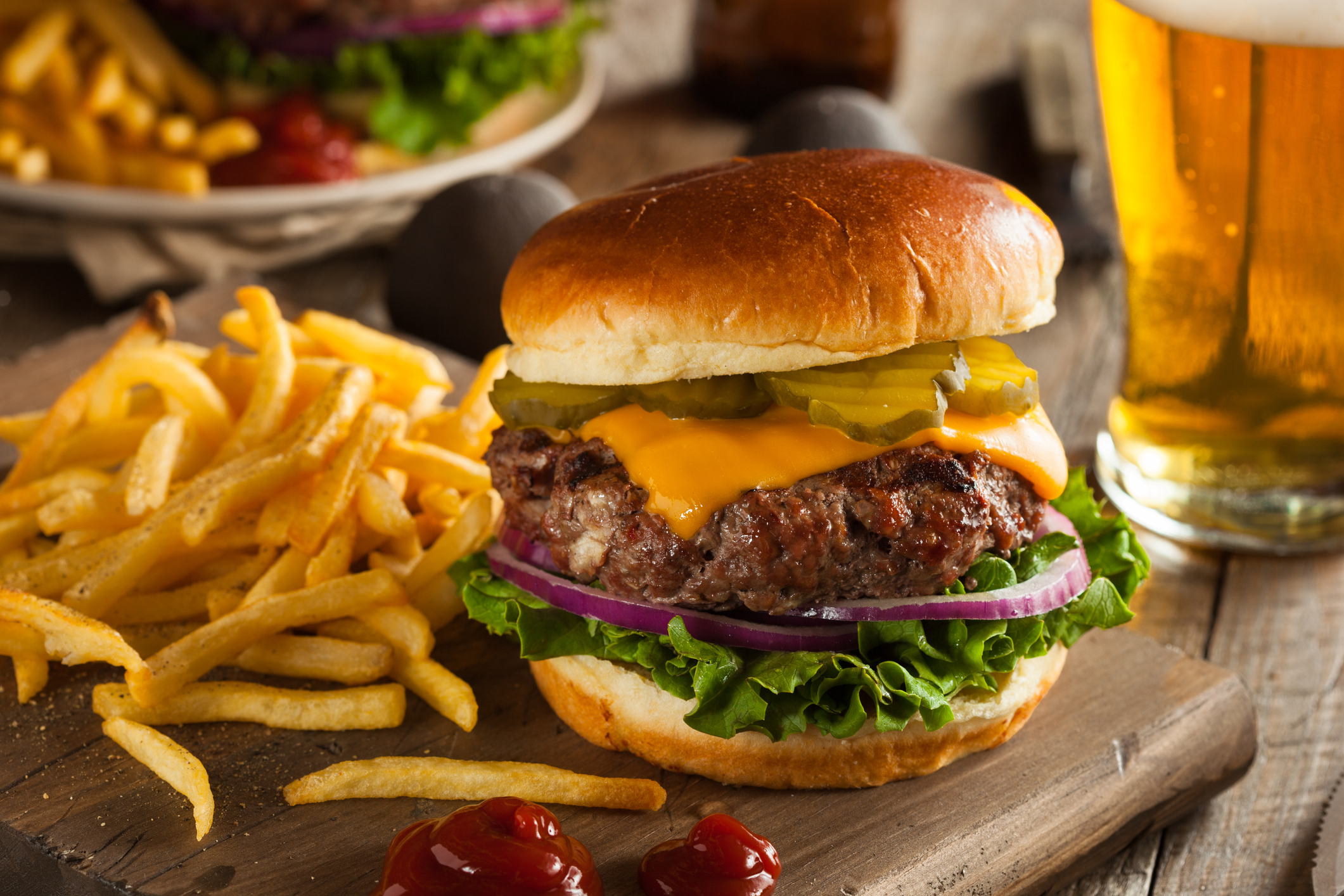 A large hamburger on a board beside a pile of fries and a glass of beer.