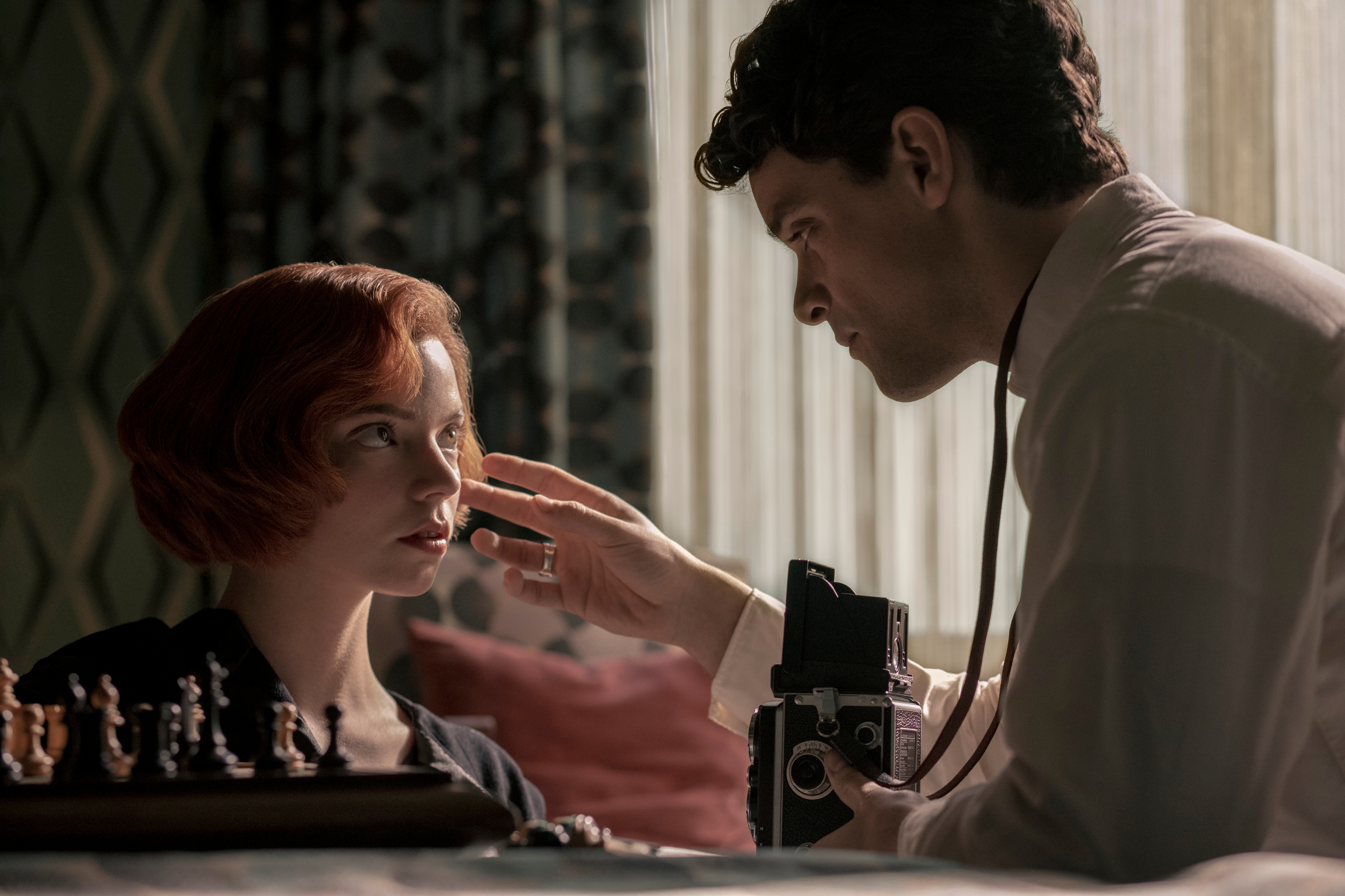 A red-headed woman (Beth) kneels before a chess board perched on the side of a bed. A brown-haired man holding a camera adjusts her hair as he prepares to photograph her.
