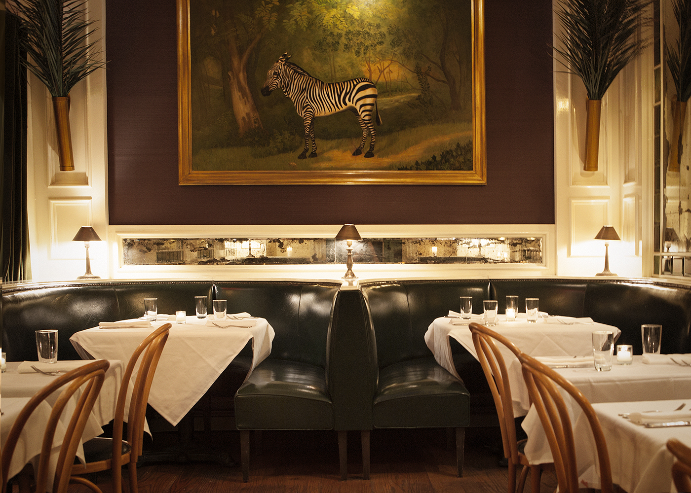 Rows of tables and chairs are organized in the dimly lit dining room of a white tablecloth restaurant. At the end of the dining room, a large photo of a zebra hangs on the wall.